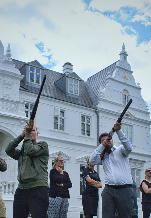En gruppe af 3 står og sigter i vejret med haglgeværer foran hotellet