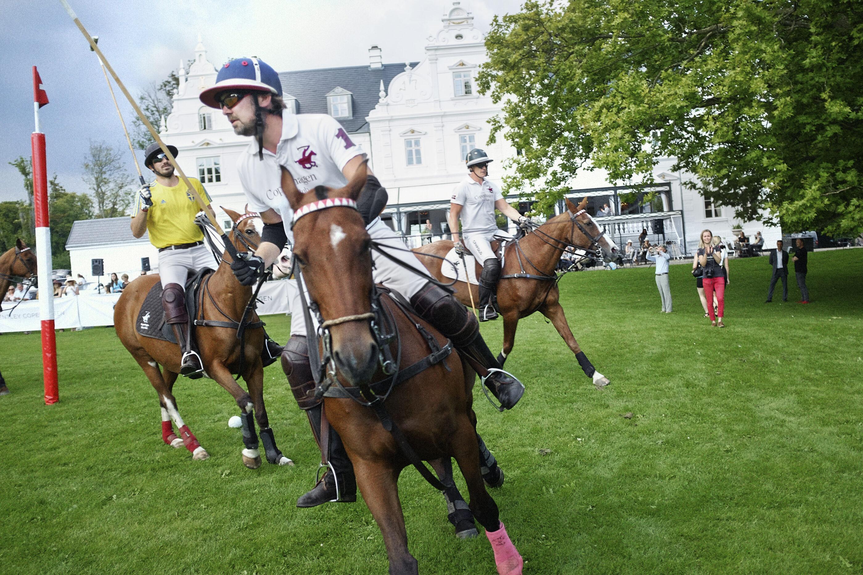 Ryttere på hest spiller Polo på Kokkedal Slots græsplæne