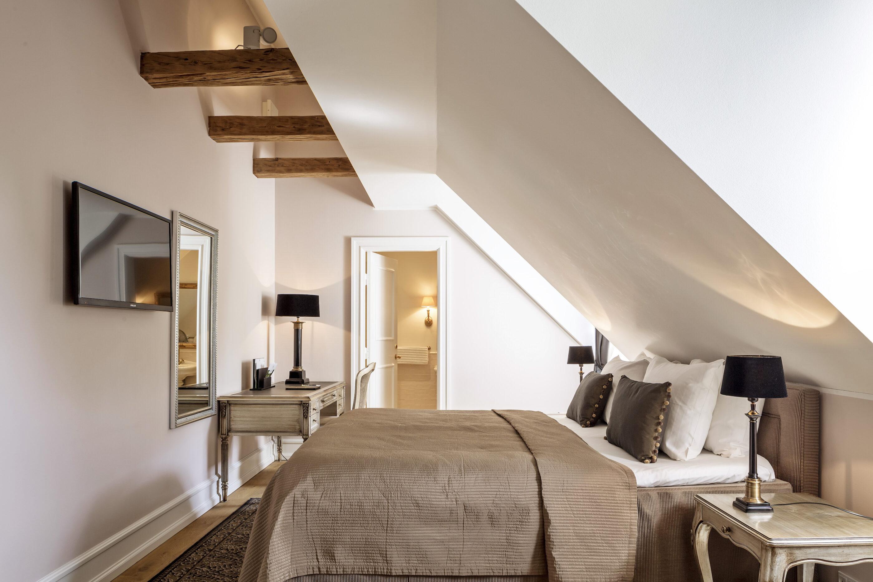 Loft-soveværelse med fladskærms TV på væggen og badeværelse i baggrunden