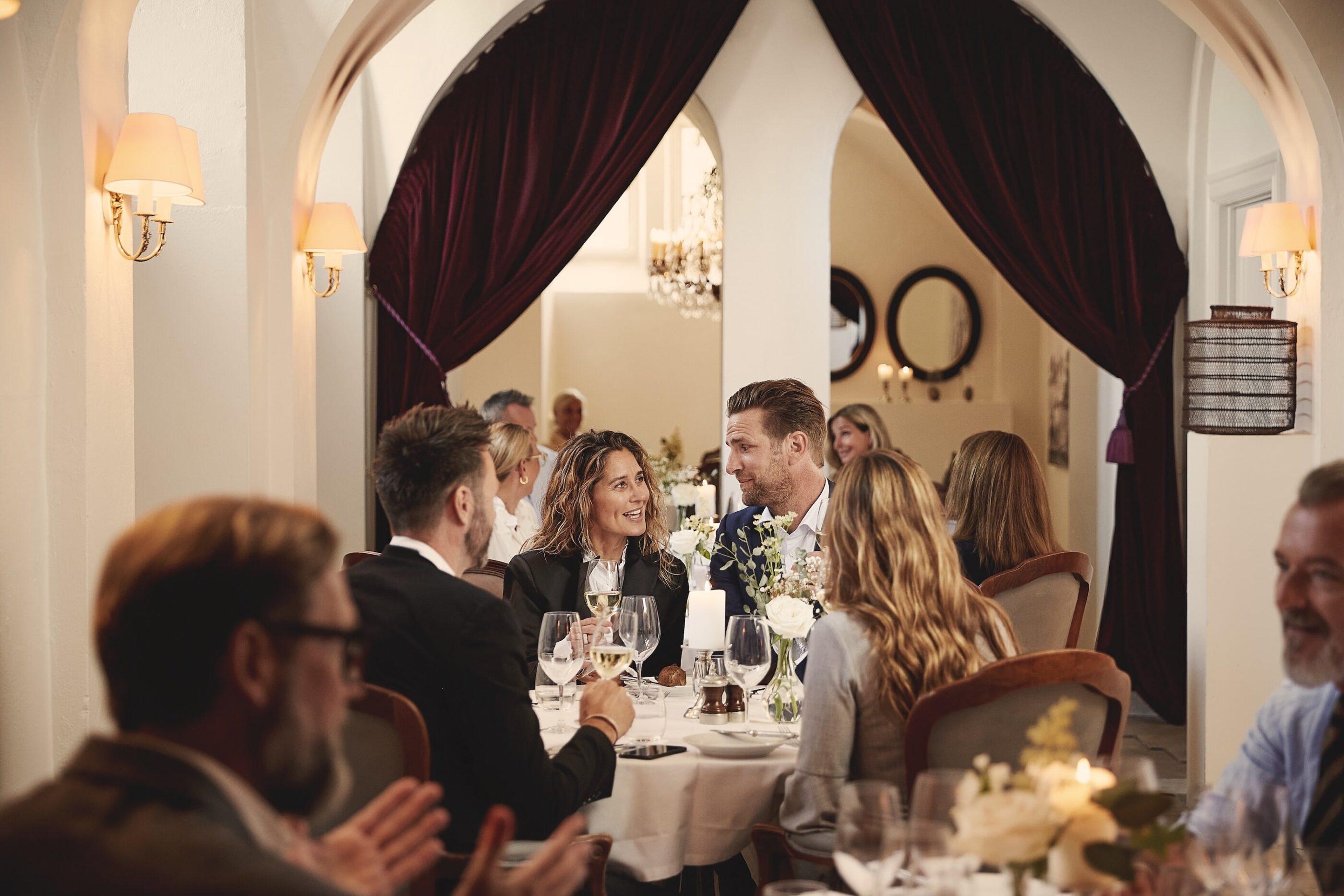2 par nyder hinandens selskab ved et lille middagsbord