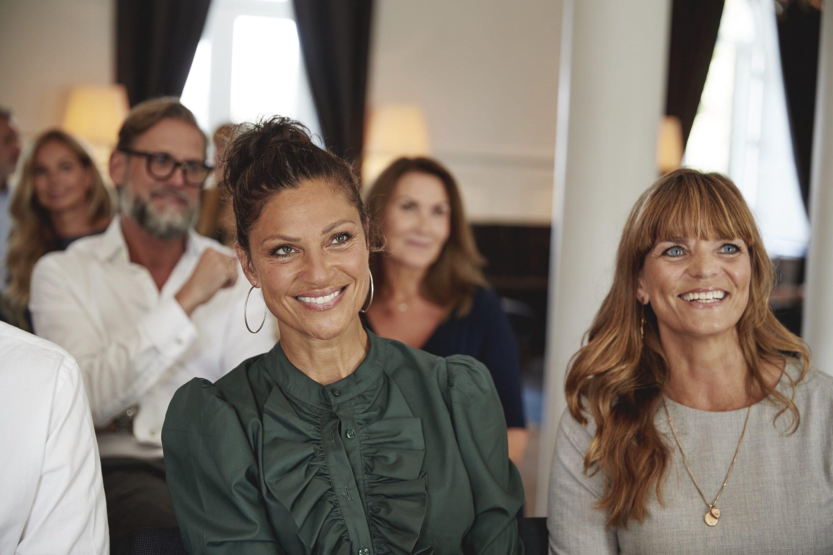 2 kvinder lytter interesseret og smilende til en underholdene præsentation