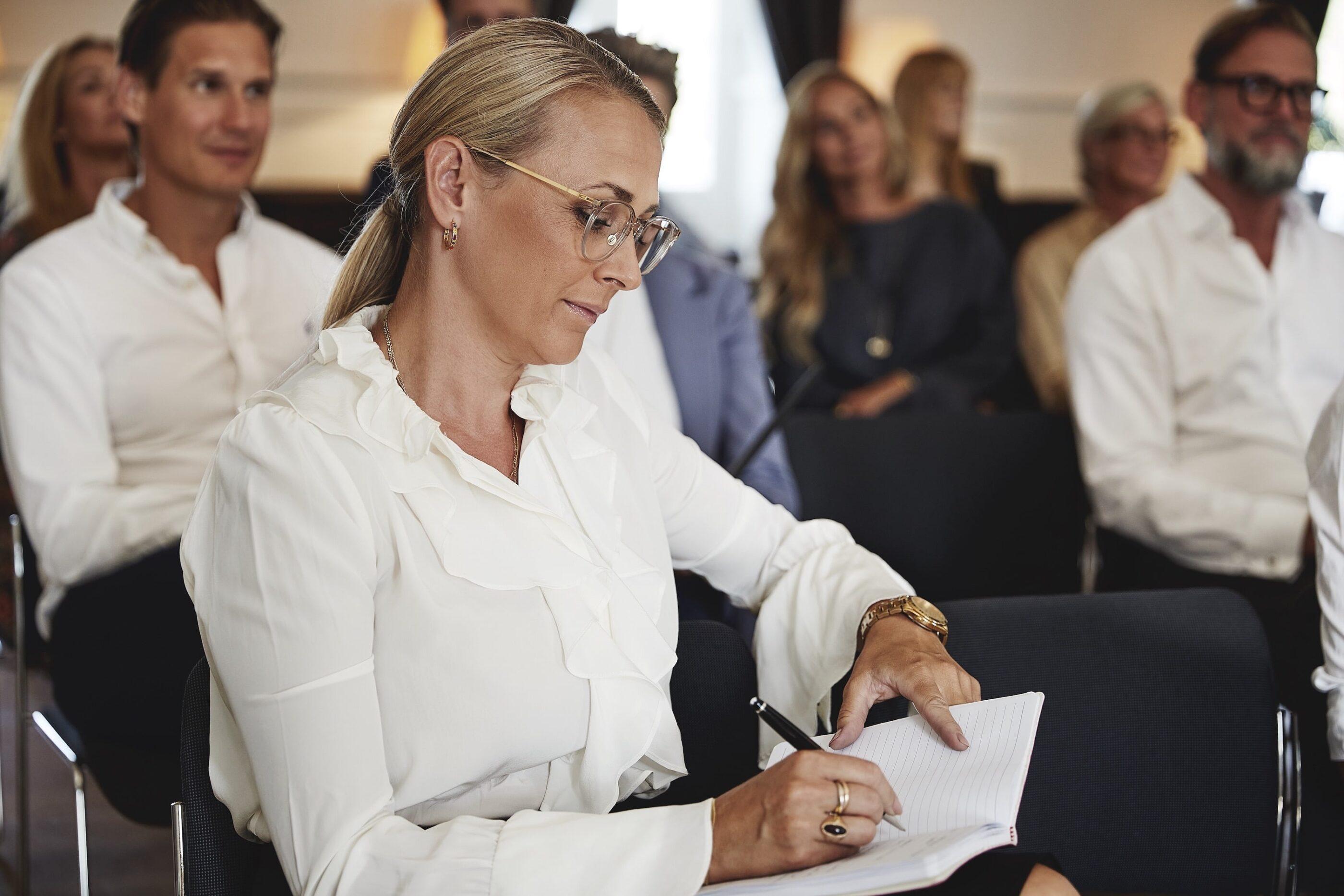 Kvinde skriver noter ned i sin notesbog under præsentationen med en flot pen.