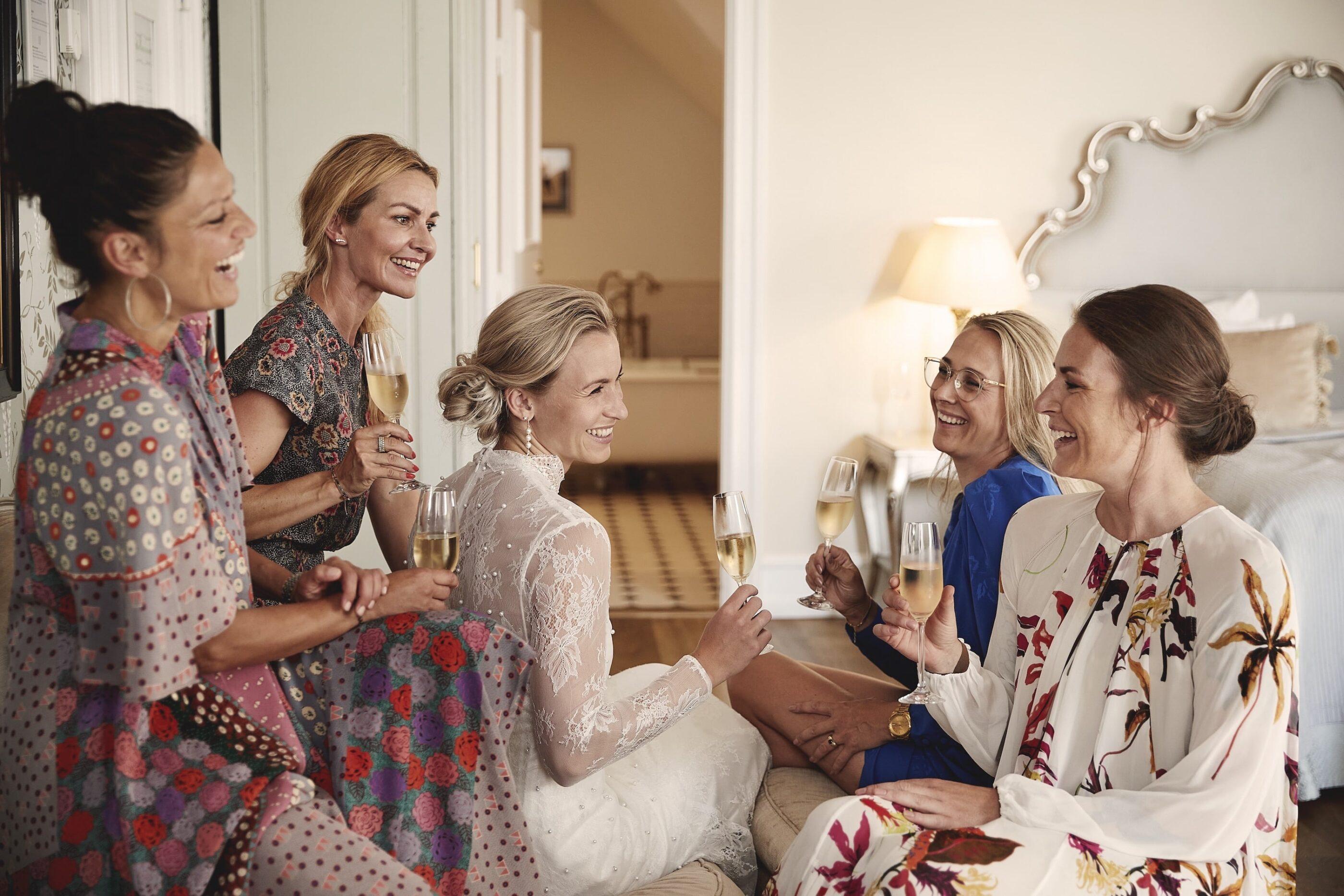 5 kvinder skåler til et glas hvidvin i soveværelset