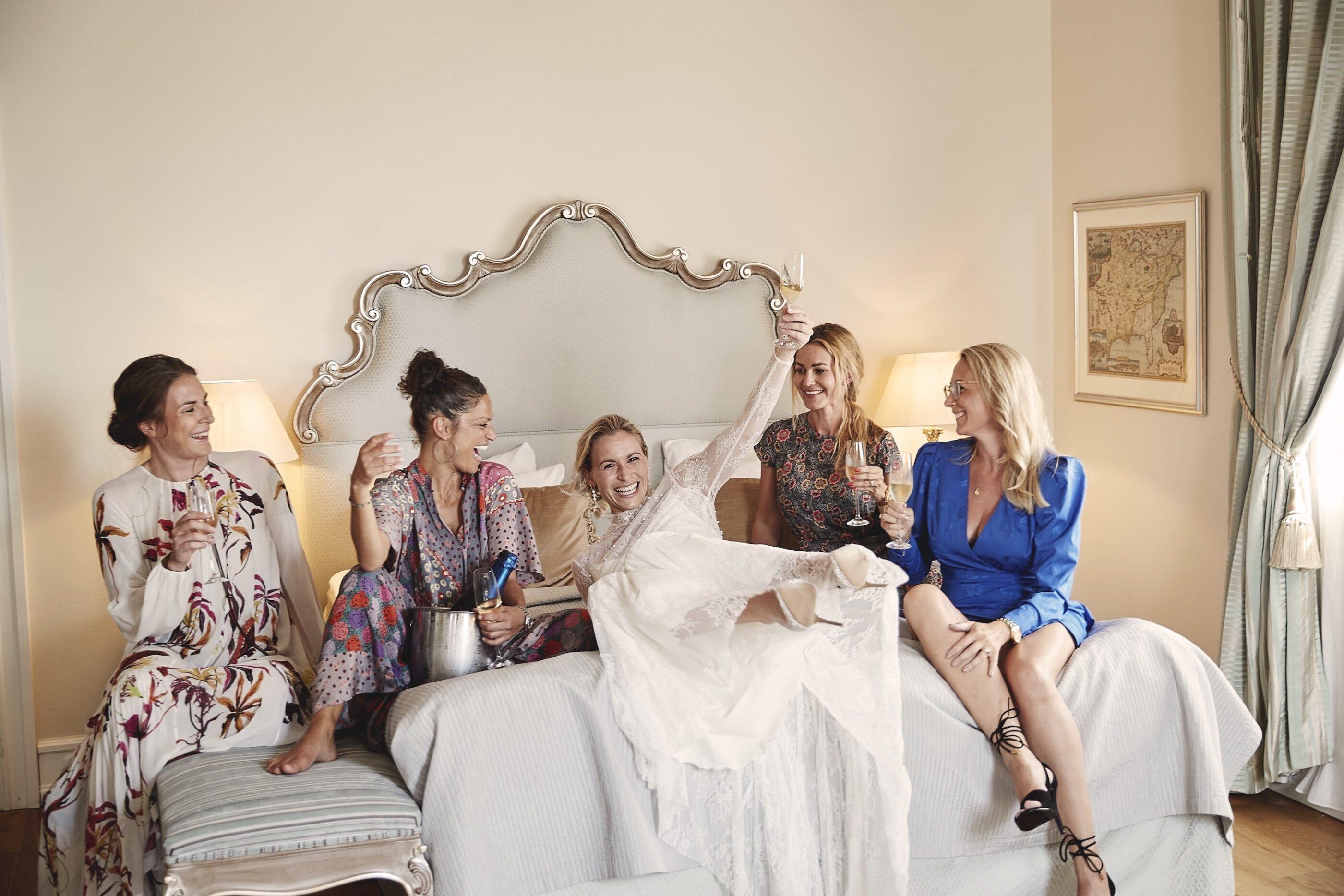 5 kvinder hygger på en seng og sengestol med vin