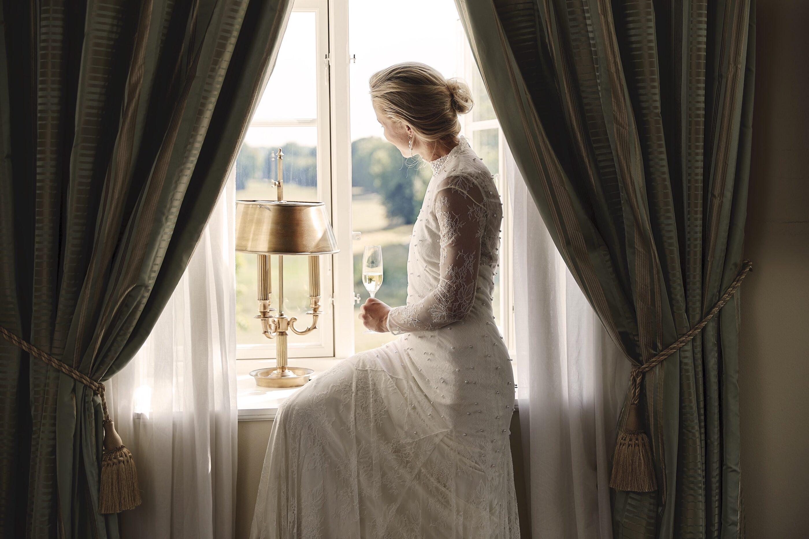 En kvinde i hvid kjole kigger ud af vinduet med et glas vin i hånden
