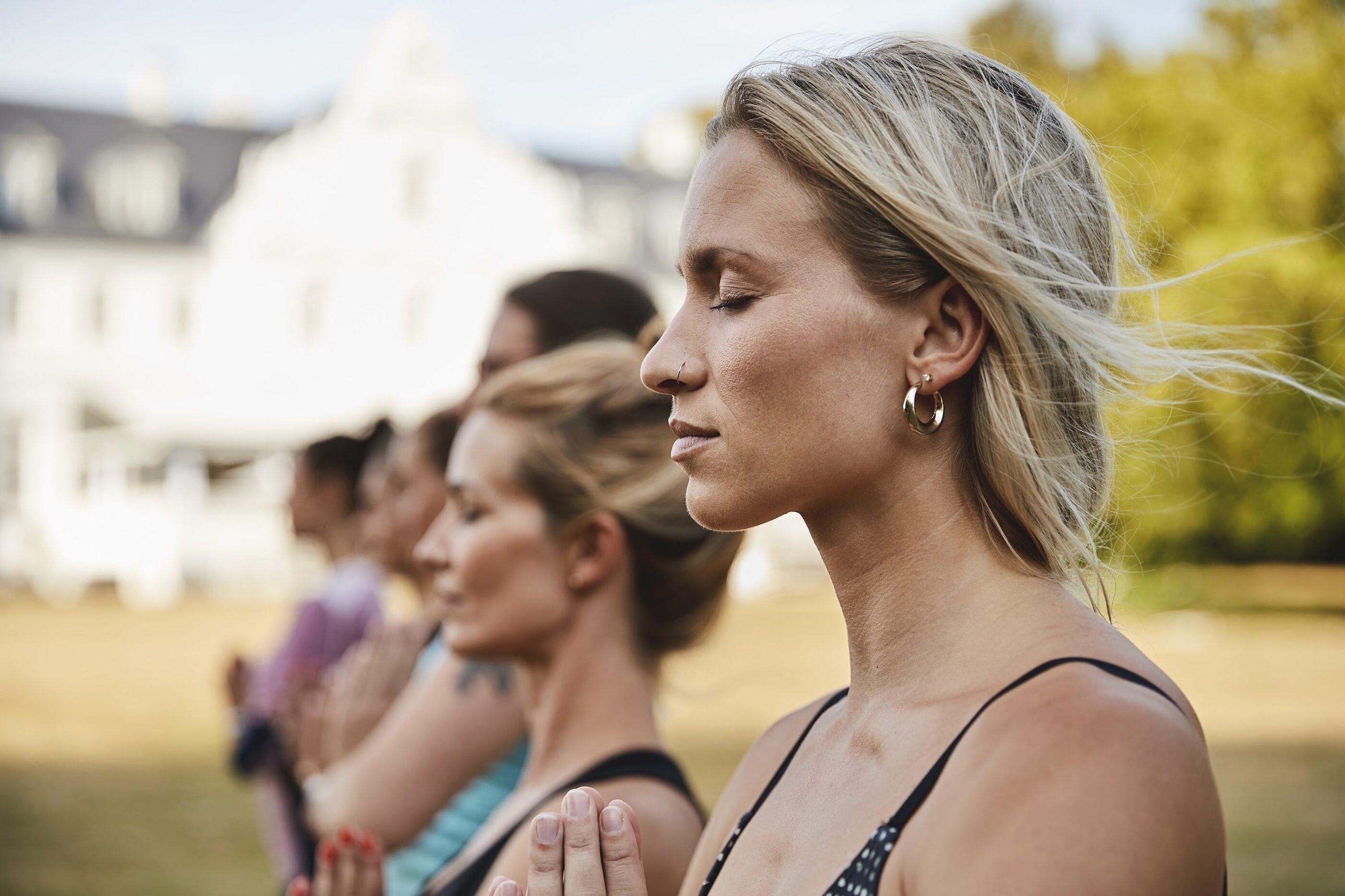 En gruppe af kvinder laver yoga udenfor i haven