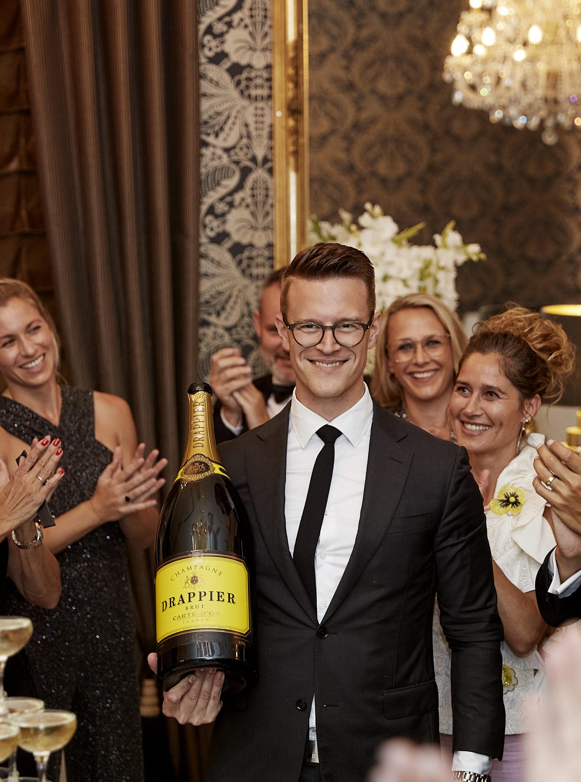 Folk klapper i en stor forsamling mens en mand bliver hyldet med en kæmpe champagne flaske