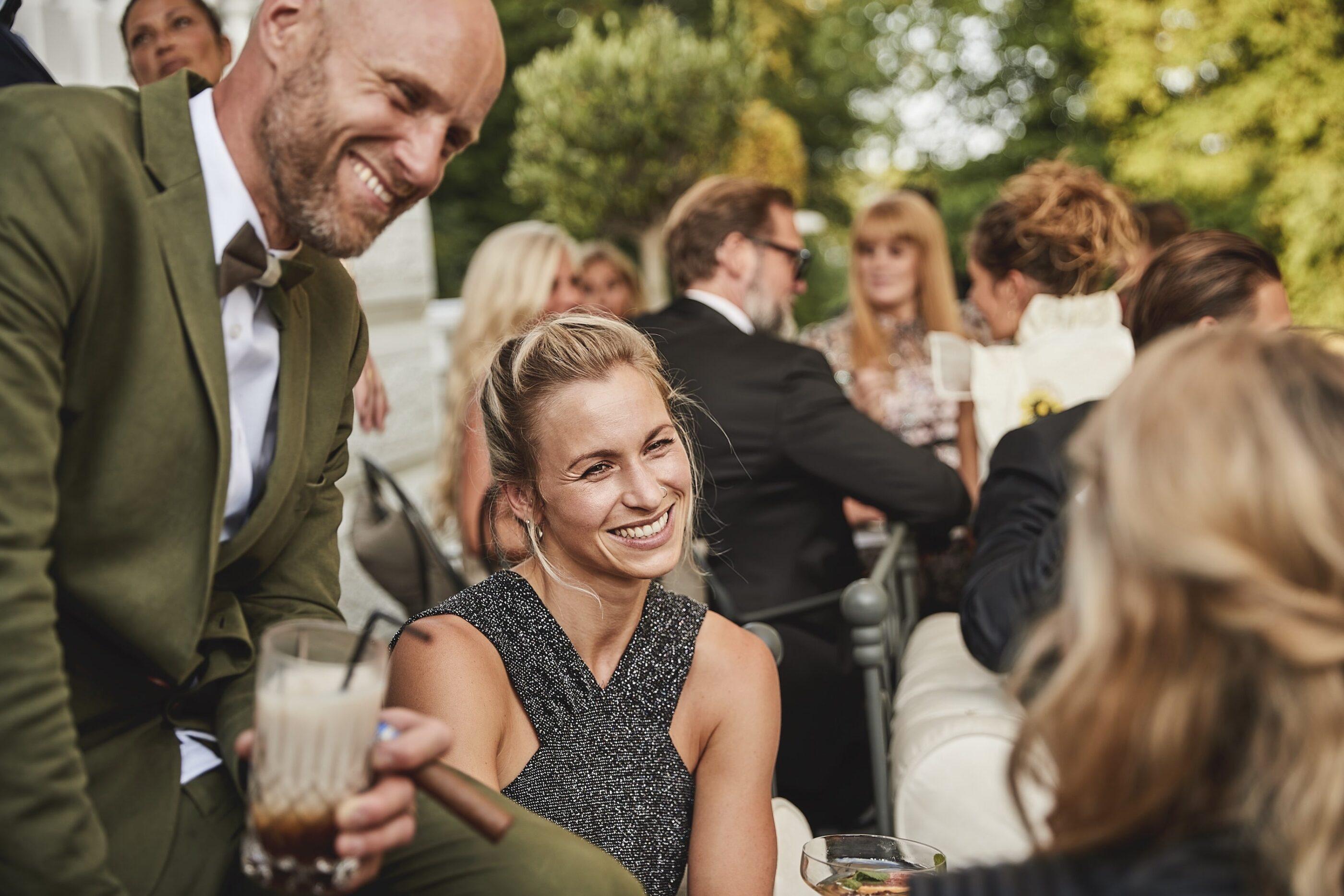 En mand og en kvinde nyder drinks og cigar og smiler udendørs blandt en masse mennesker