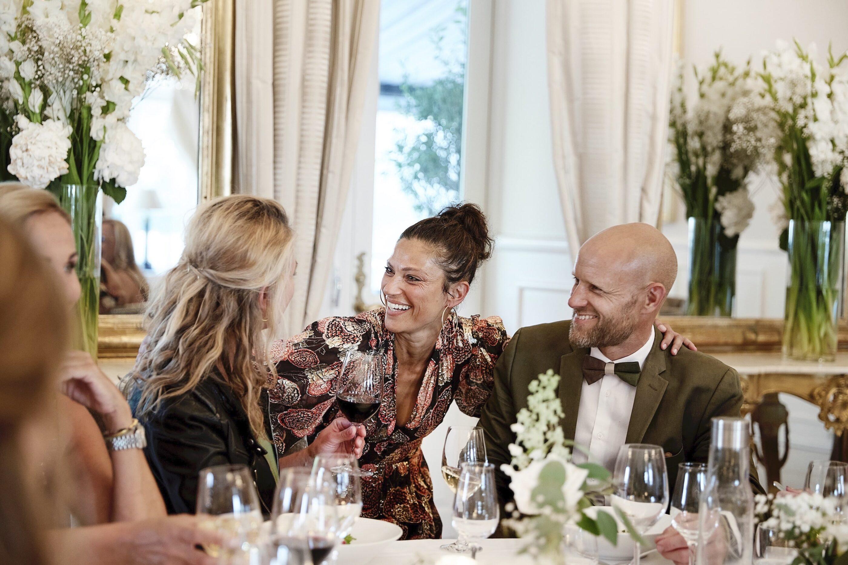 3 mennesker snakker og drikker rødvin ved middagsbordet