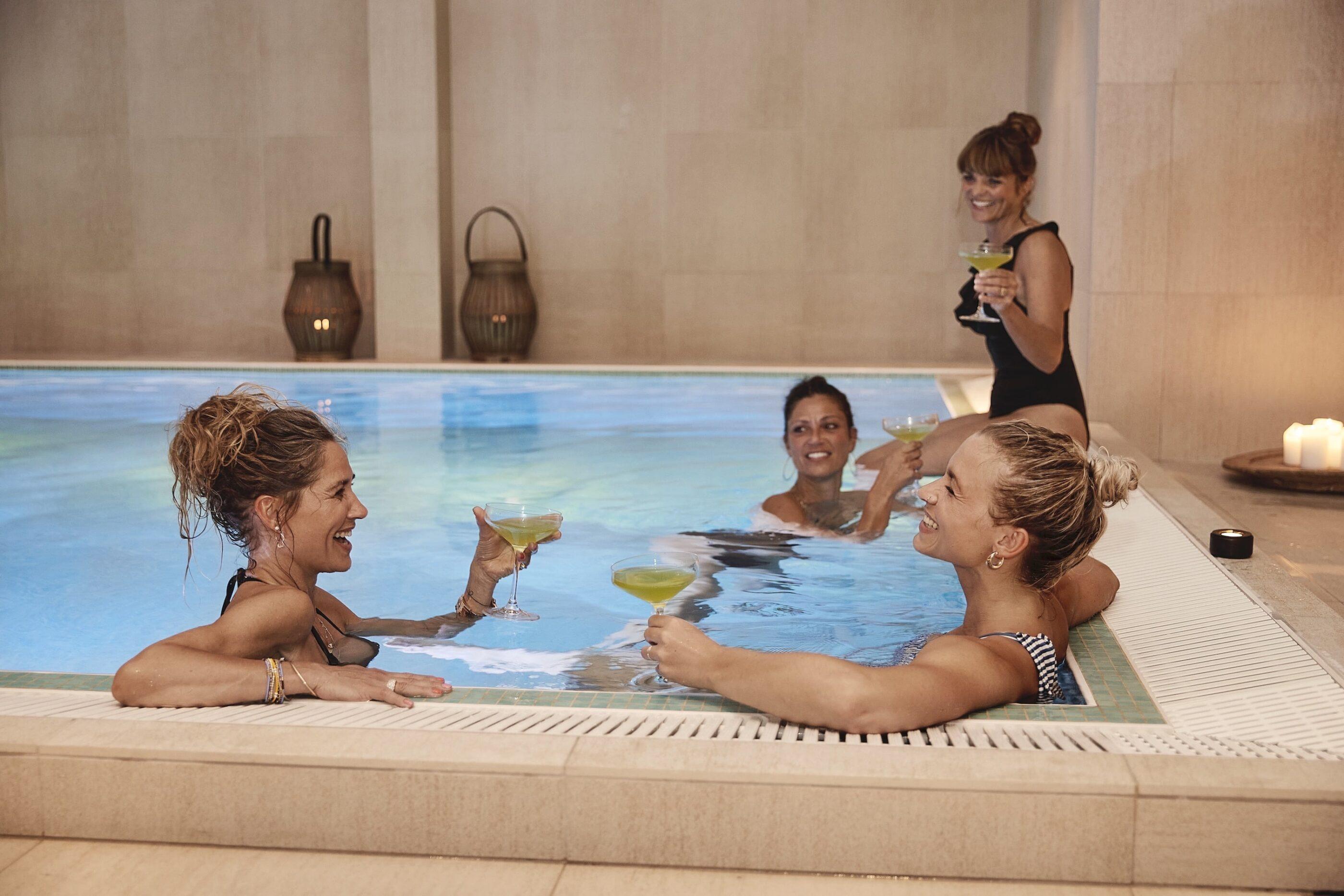 4 kvinder drikker cocktails mens de hygger i poolen