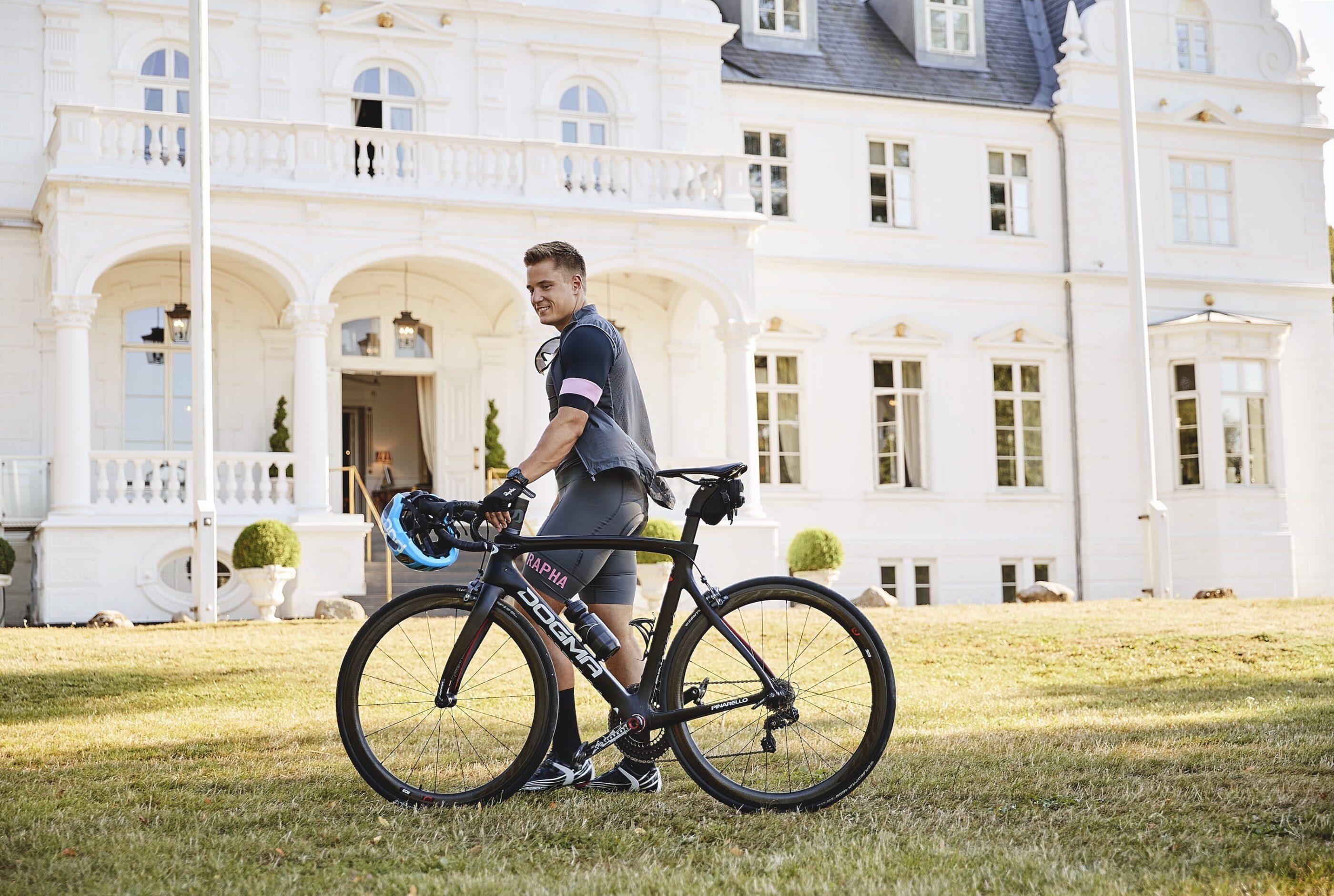 En mand iklædt cykeltøj står ude i slottets have med en sportscykel