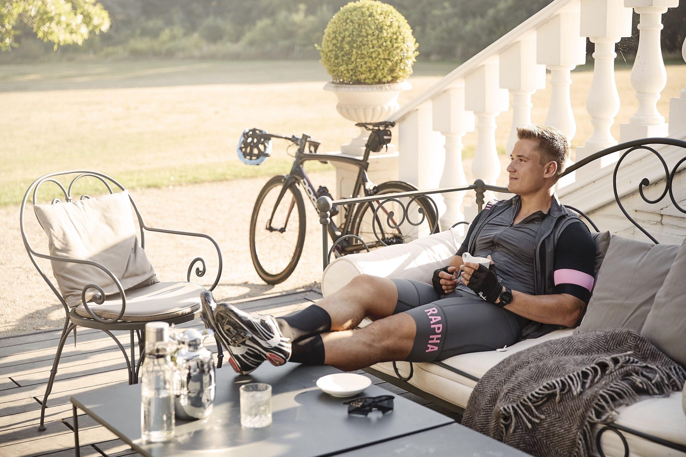 En mand iført cykeltøj slapper af på sofaen ved hotellets indgang med benene op på bordet og en varm drink i hånden
