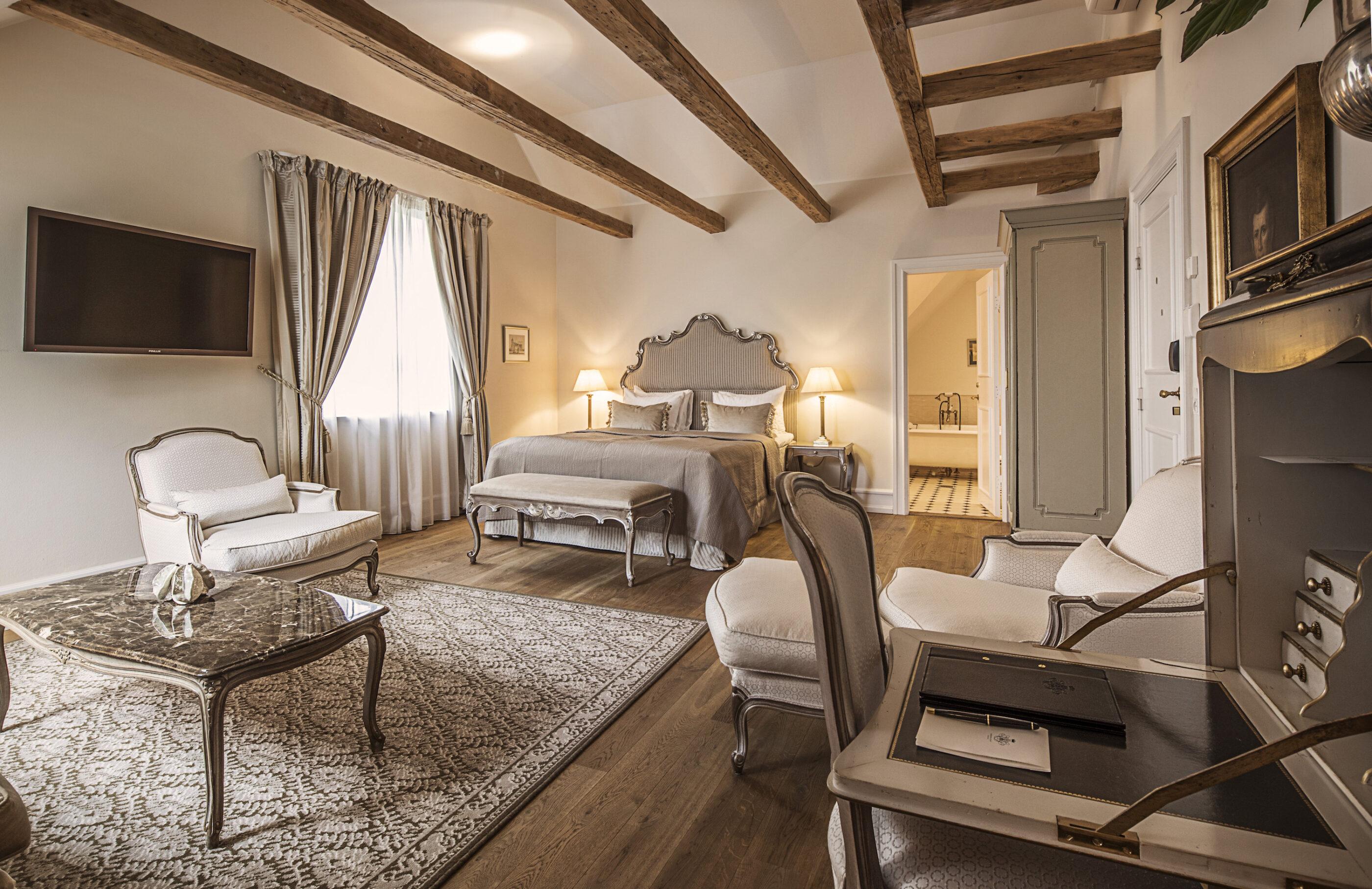 Stor suite med luksuriøs indretning, en liggestol, stort tæppe, og klassisk designet skrivebord, med fin pen, papir, og læder foldemappe.