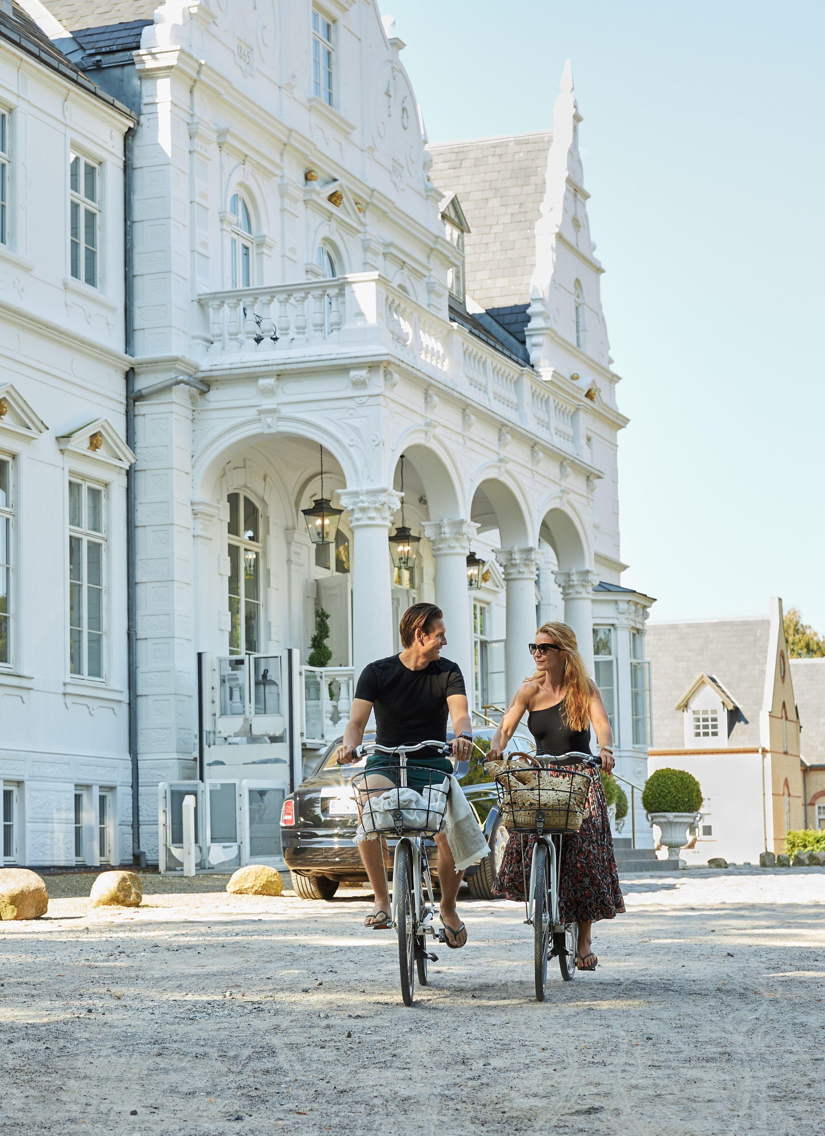 En mand og en kvinde er ved at starte en hyggelig cykeltur med hotellet i baggrunden