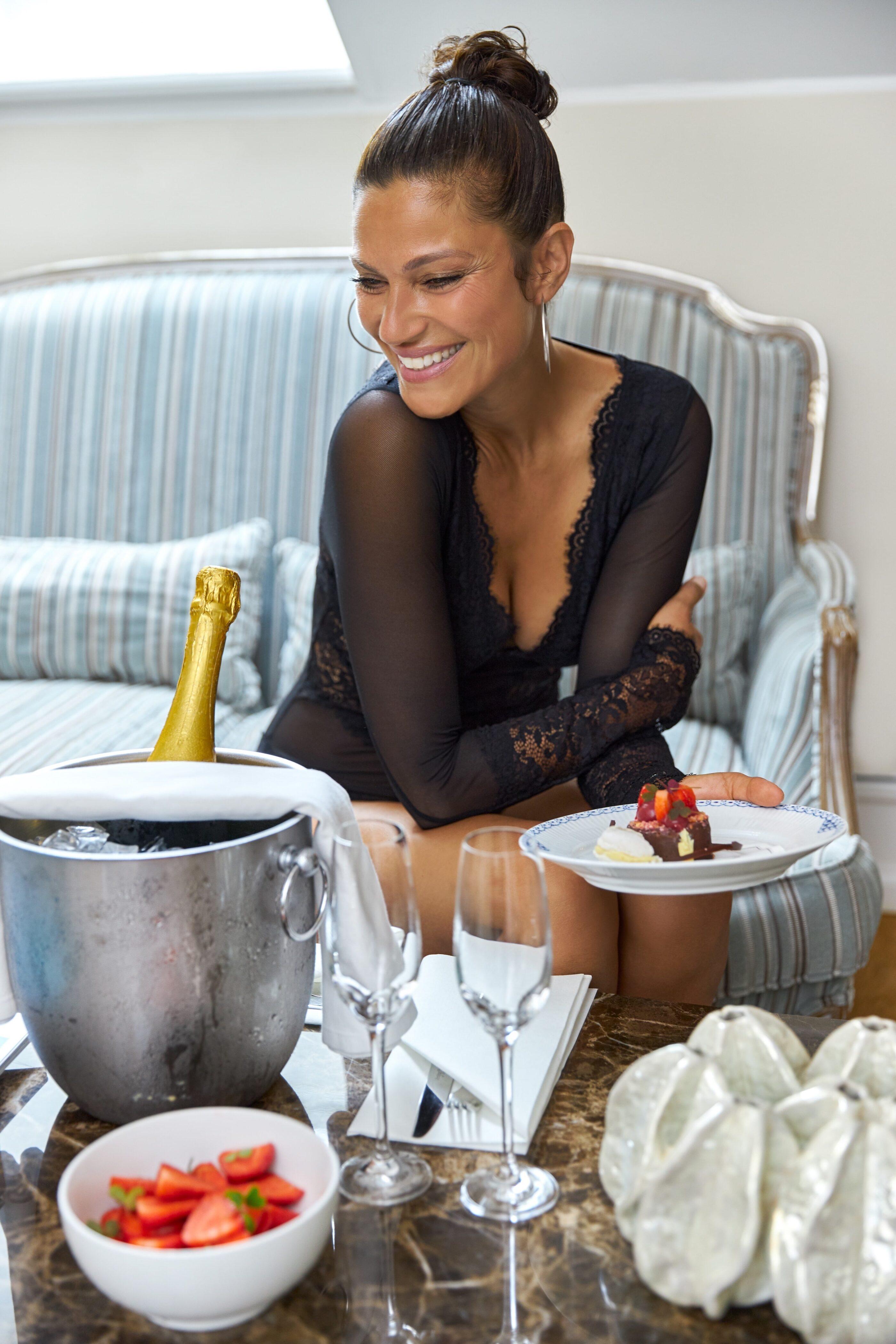 En kvinde i lingerie nyder en kage mens hun har vin på køl og 2 glas stående på bordet