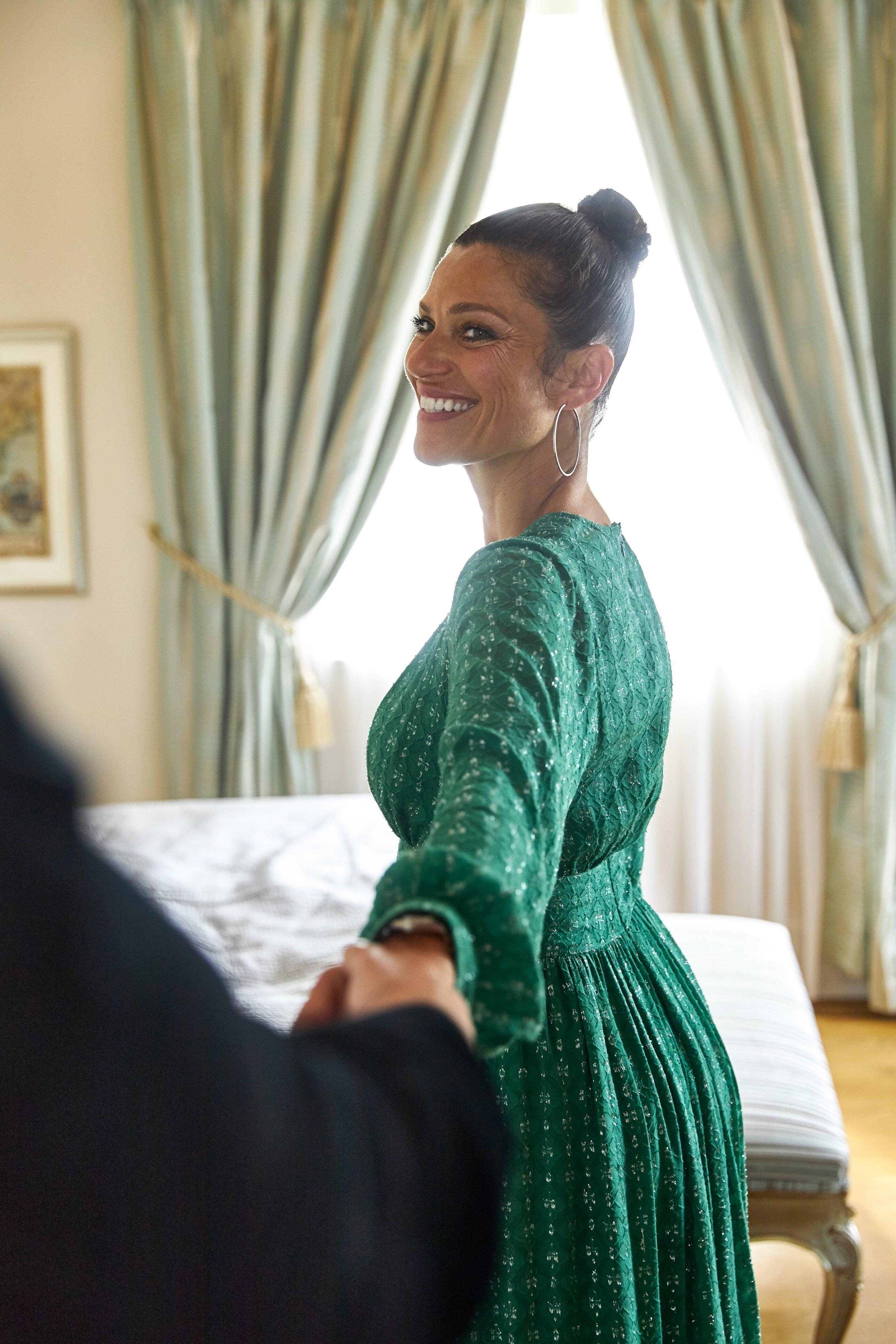 En kvinde i grøn kjole smiler med håndstrakt arm som bliver holdt af en mand