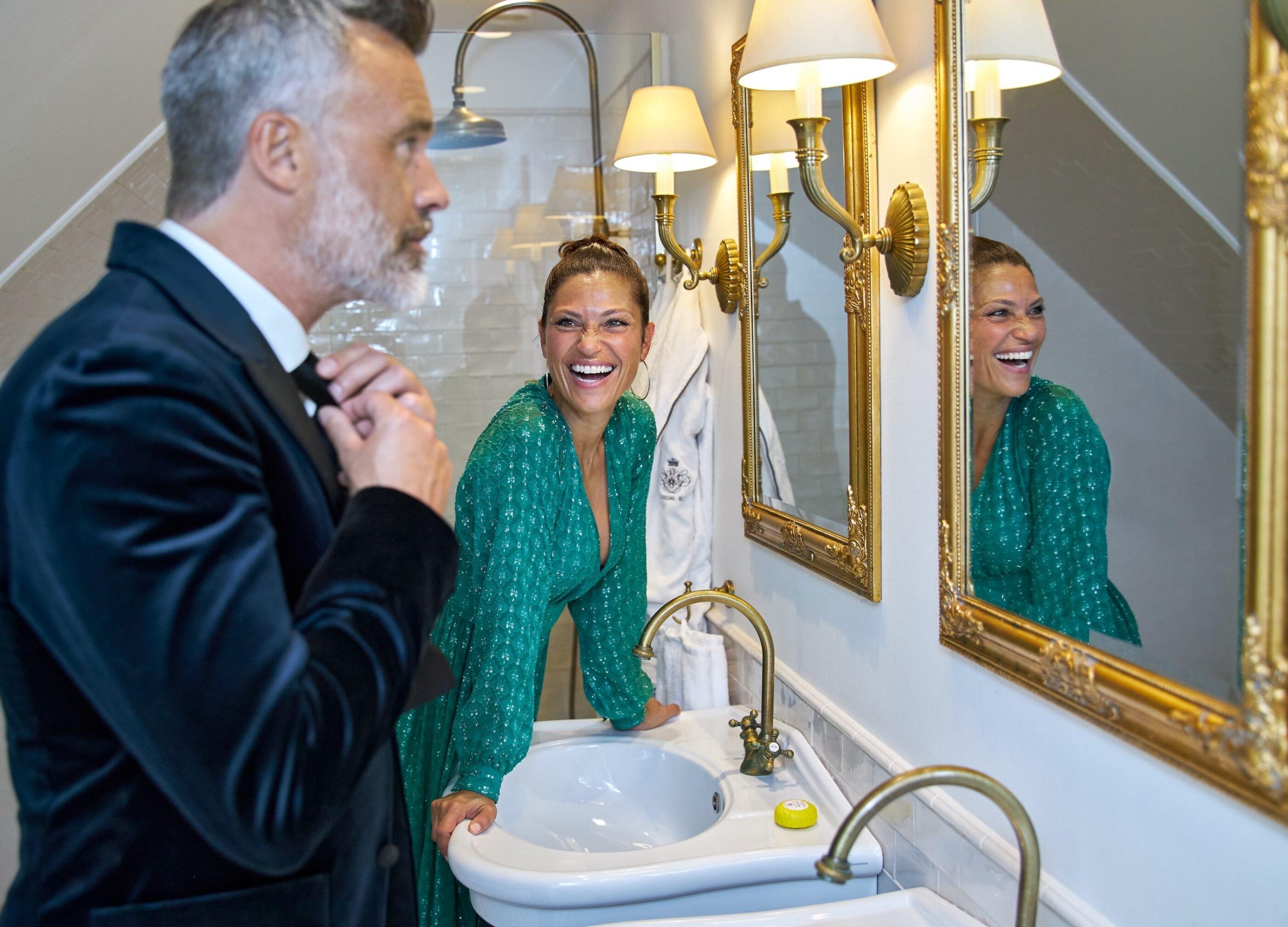 En mand gør sig klar i badeværelset foran spejlet og fikser sin butterfly mens en kvinde i grøn kjole griner