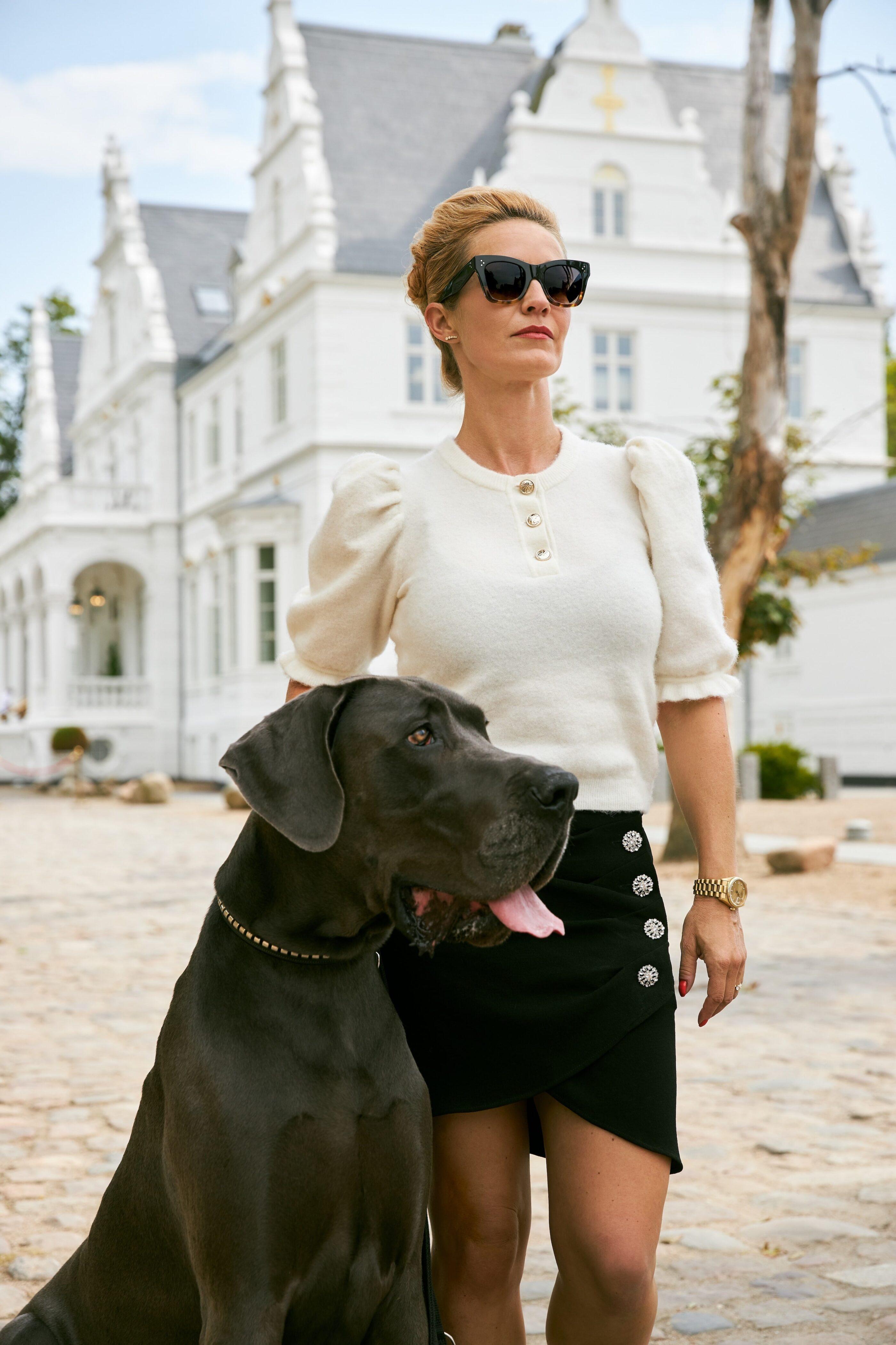 En kvinde står foran slottet med sin hund og kigger på noget