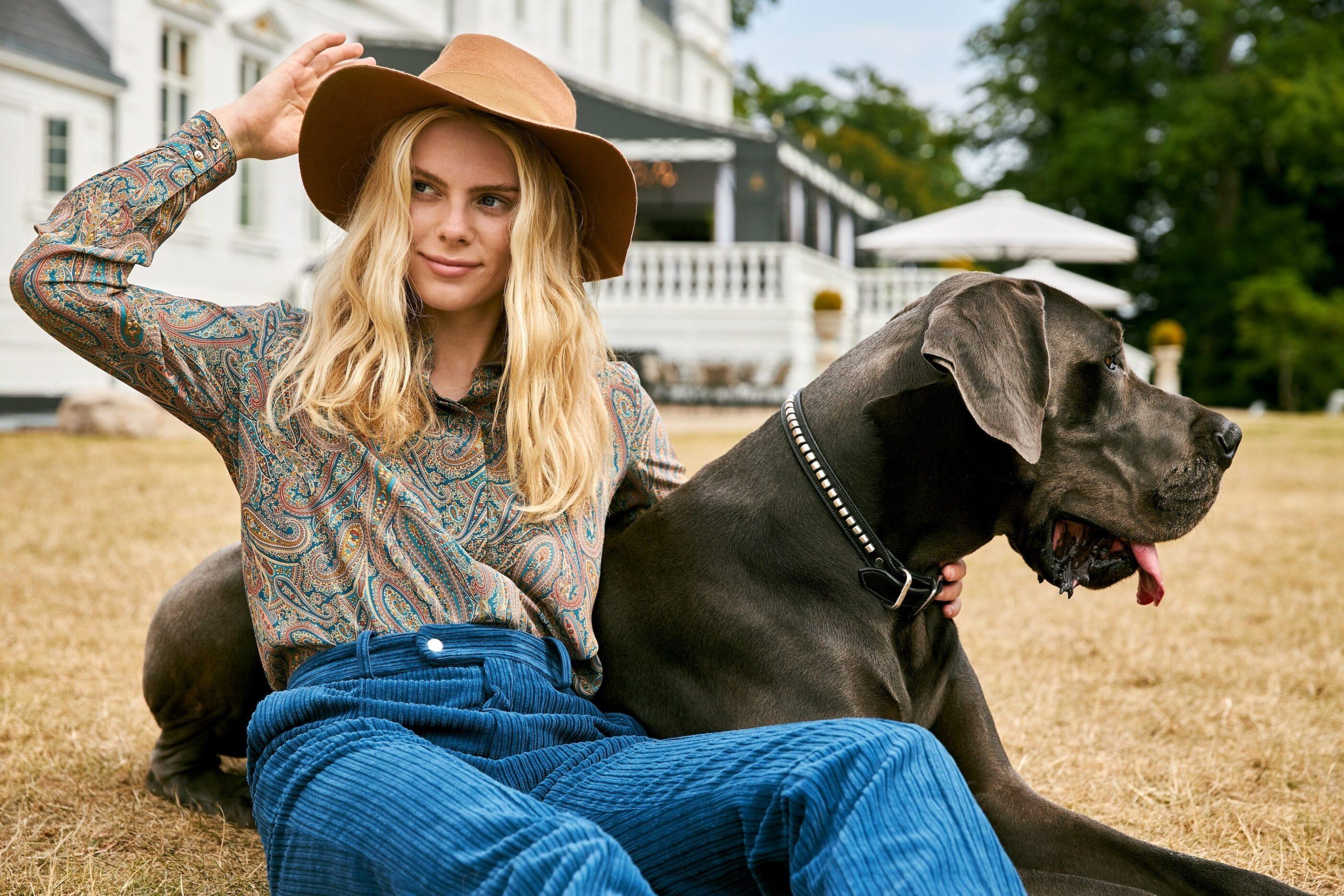 En kvinde med cowboyhat sidder i haven med en hund