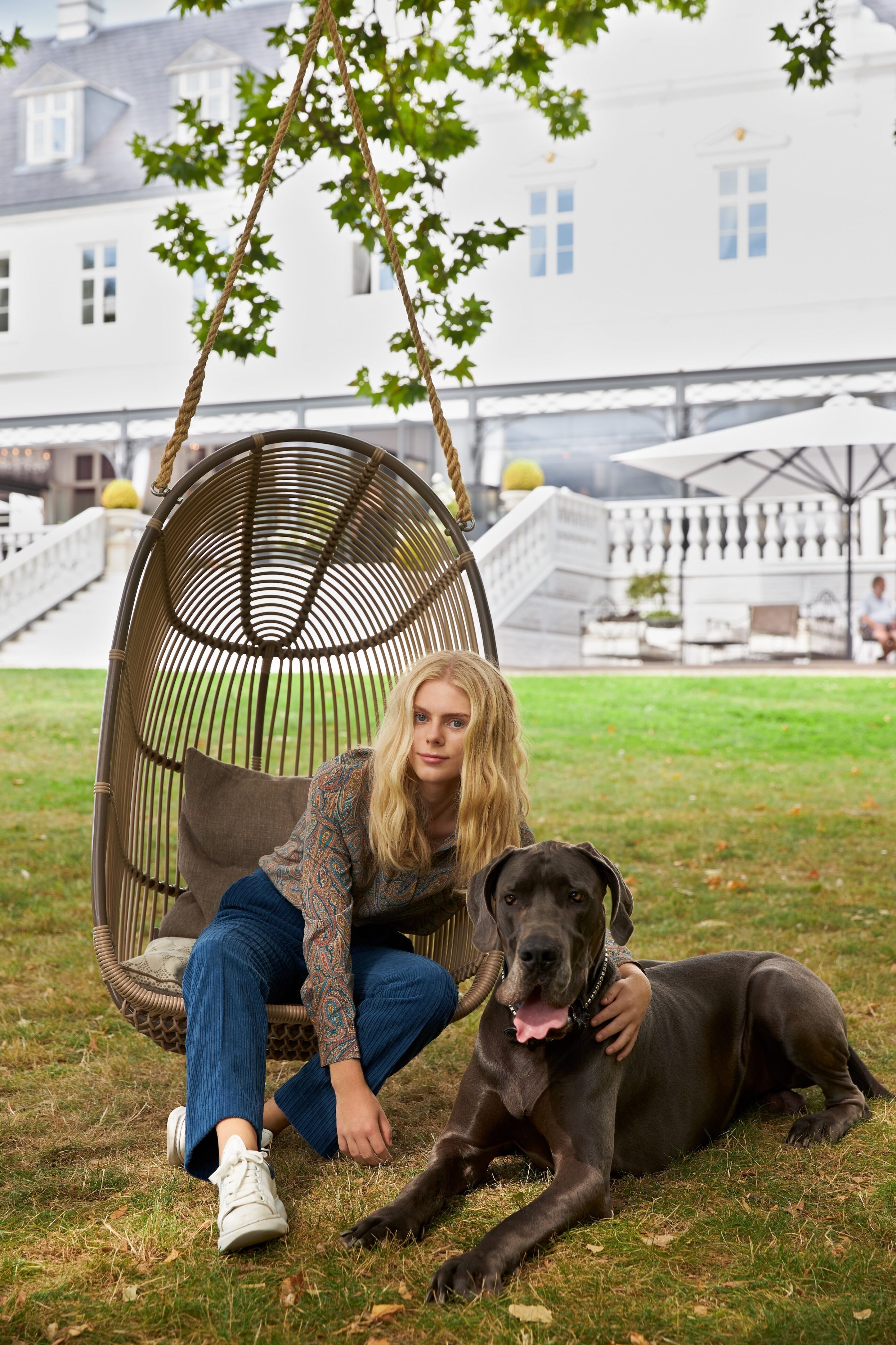 En kvinde sidder på en havestol som hænger under et træ, mens hun kæler en hund
