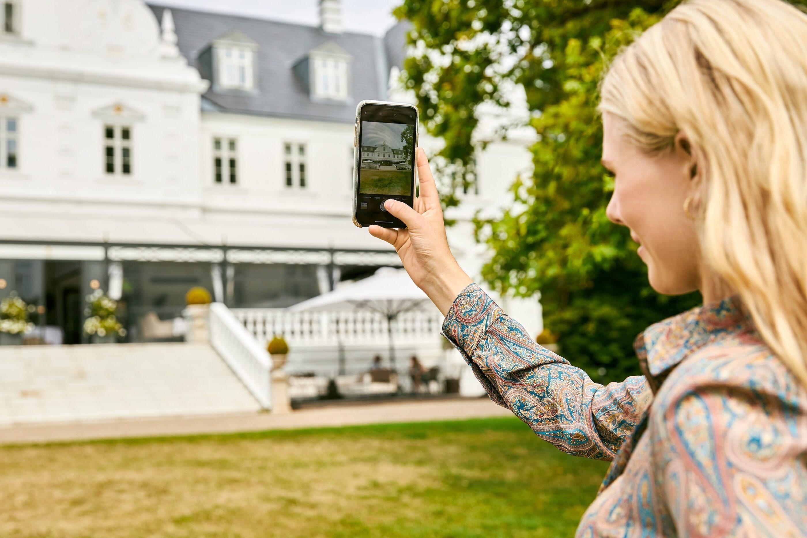 En kvinde står i haven og tager et billede af Kokkedal slot