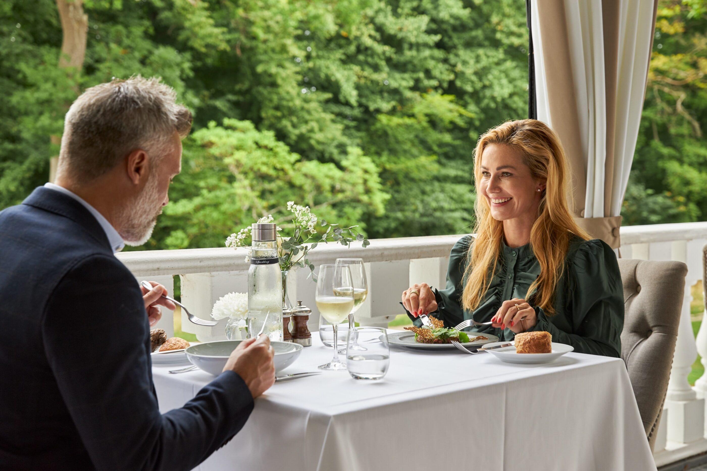 En mand og kvinde nyder frokost middag og vin ved terassen