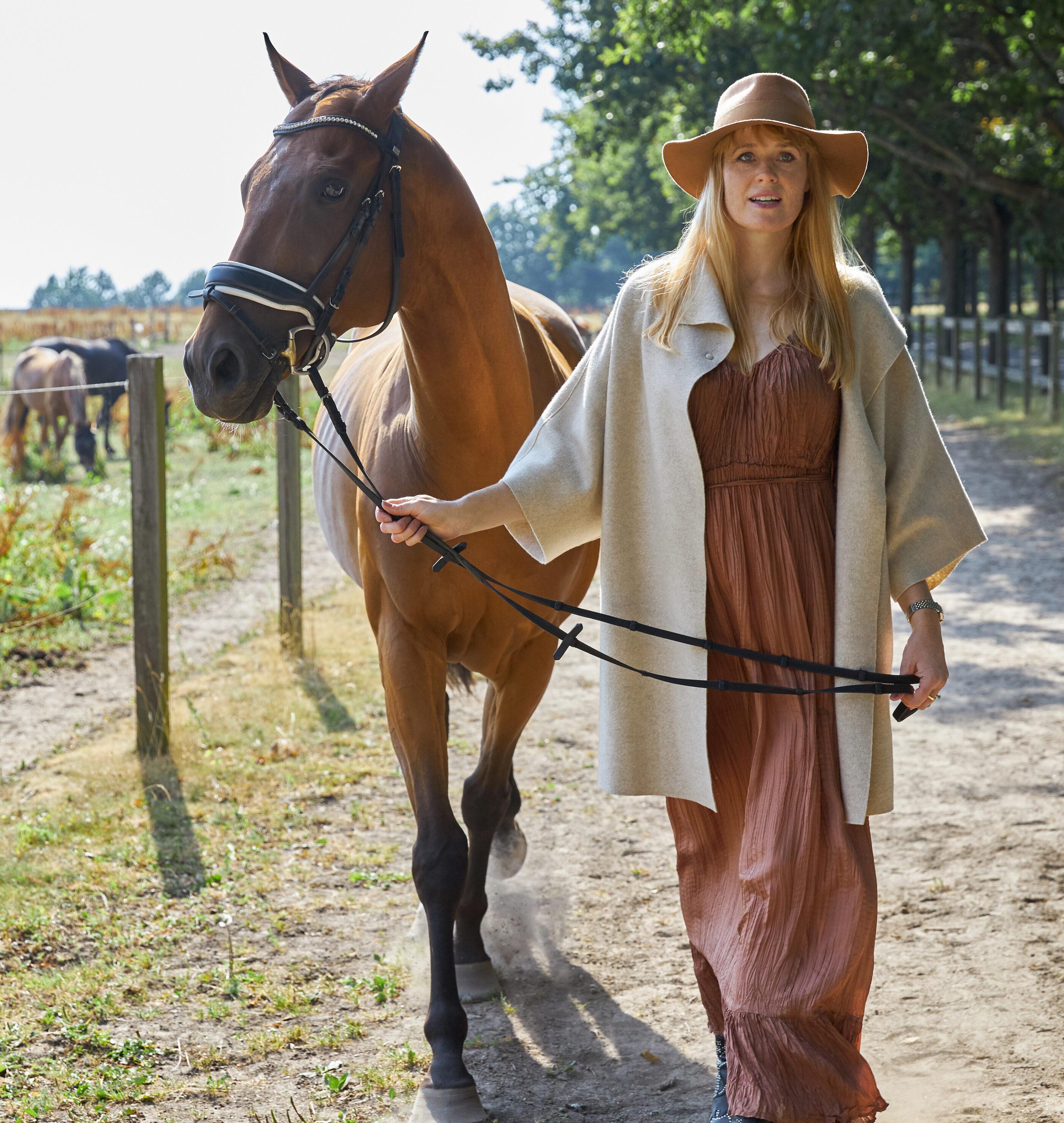 En kvinde går ned ad en riddebane med sin hest