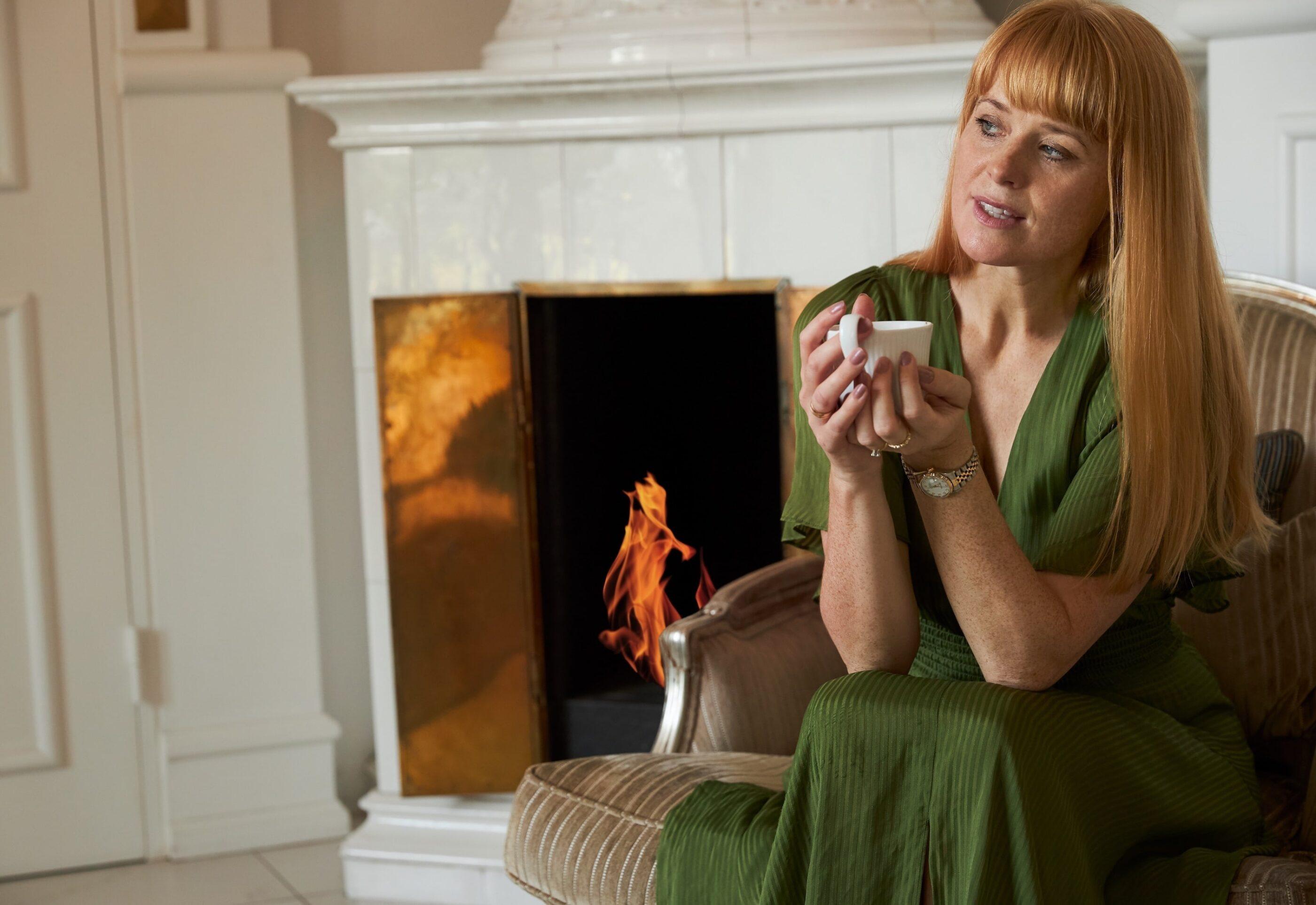 En kvinde i grøn kjole nyder en varm drik ved ildstedet