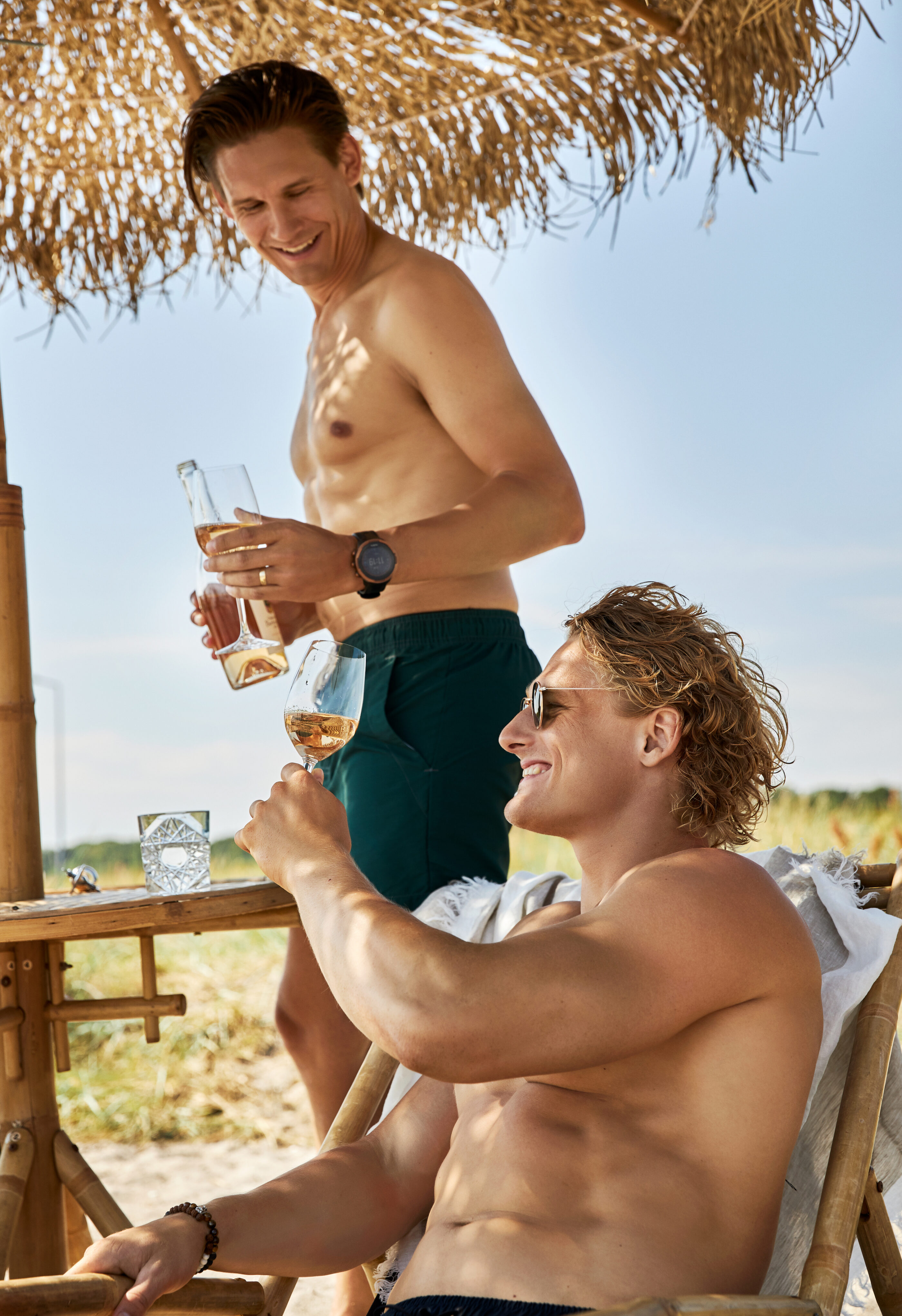 Two men drinking wine at the beach