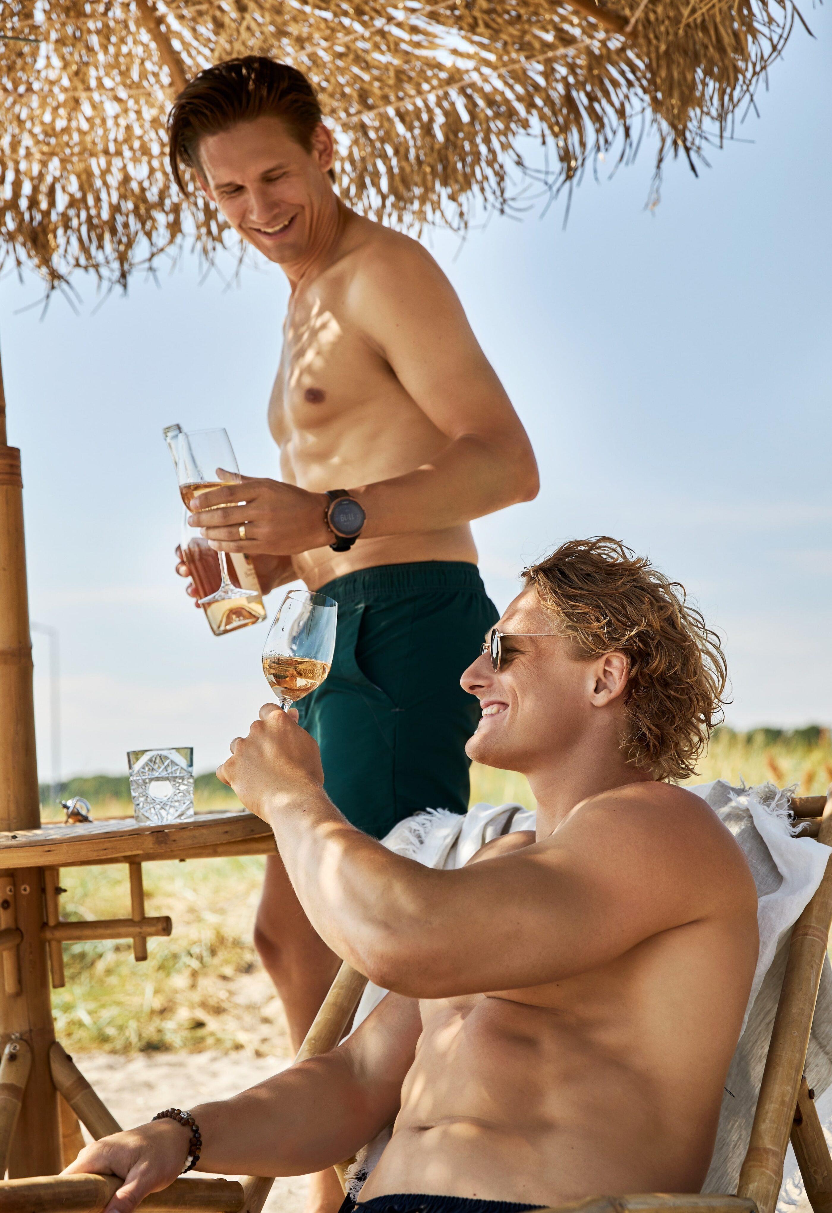 2 mænd er ved stranden i shorts og skåler