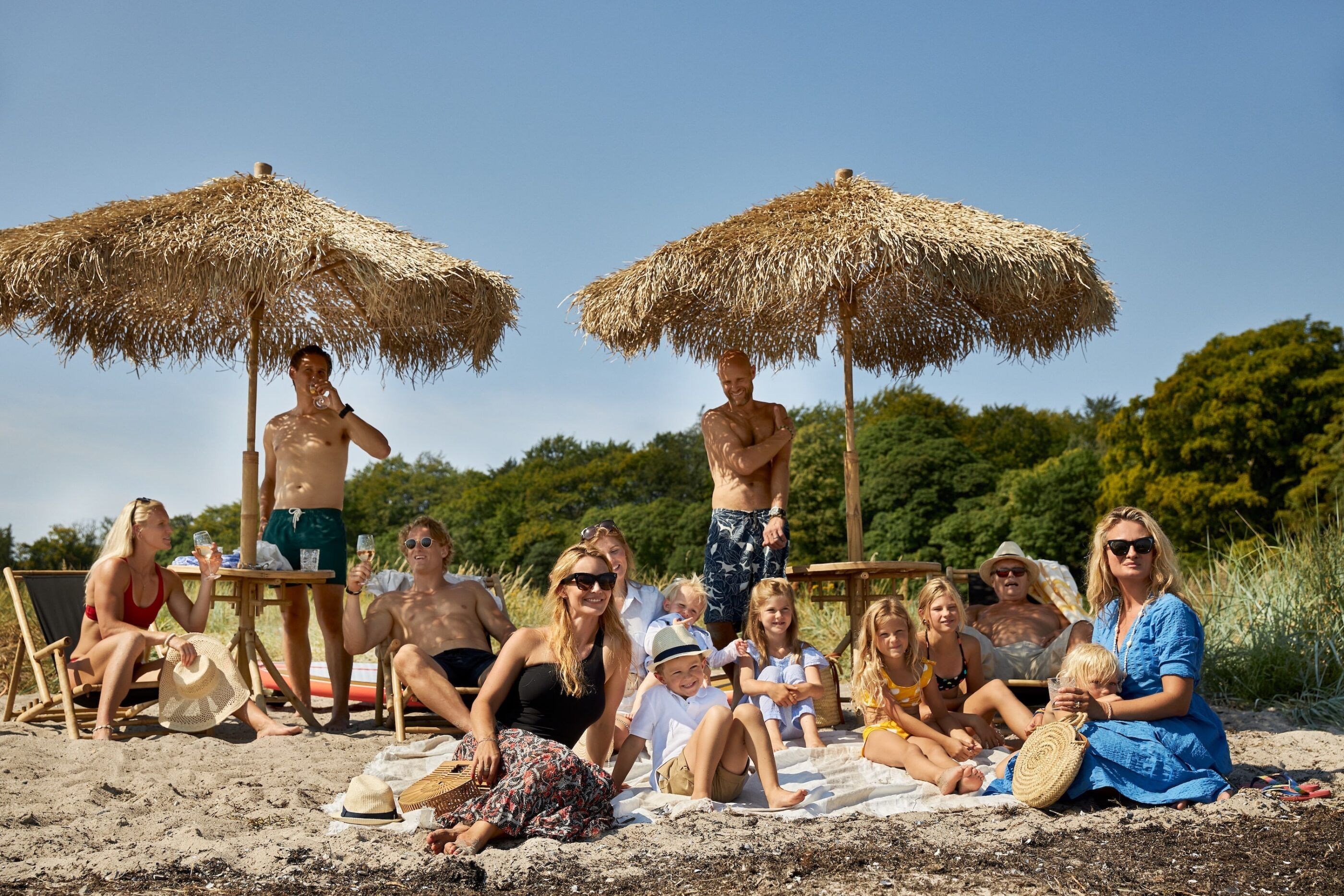 Flere mennesker er samlet på en strand, både børn og voksne, som begge smiler af noget i horizonten