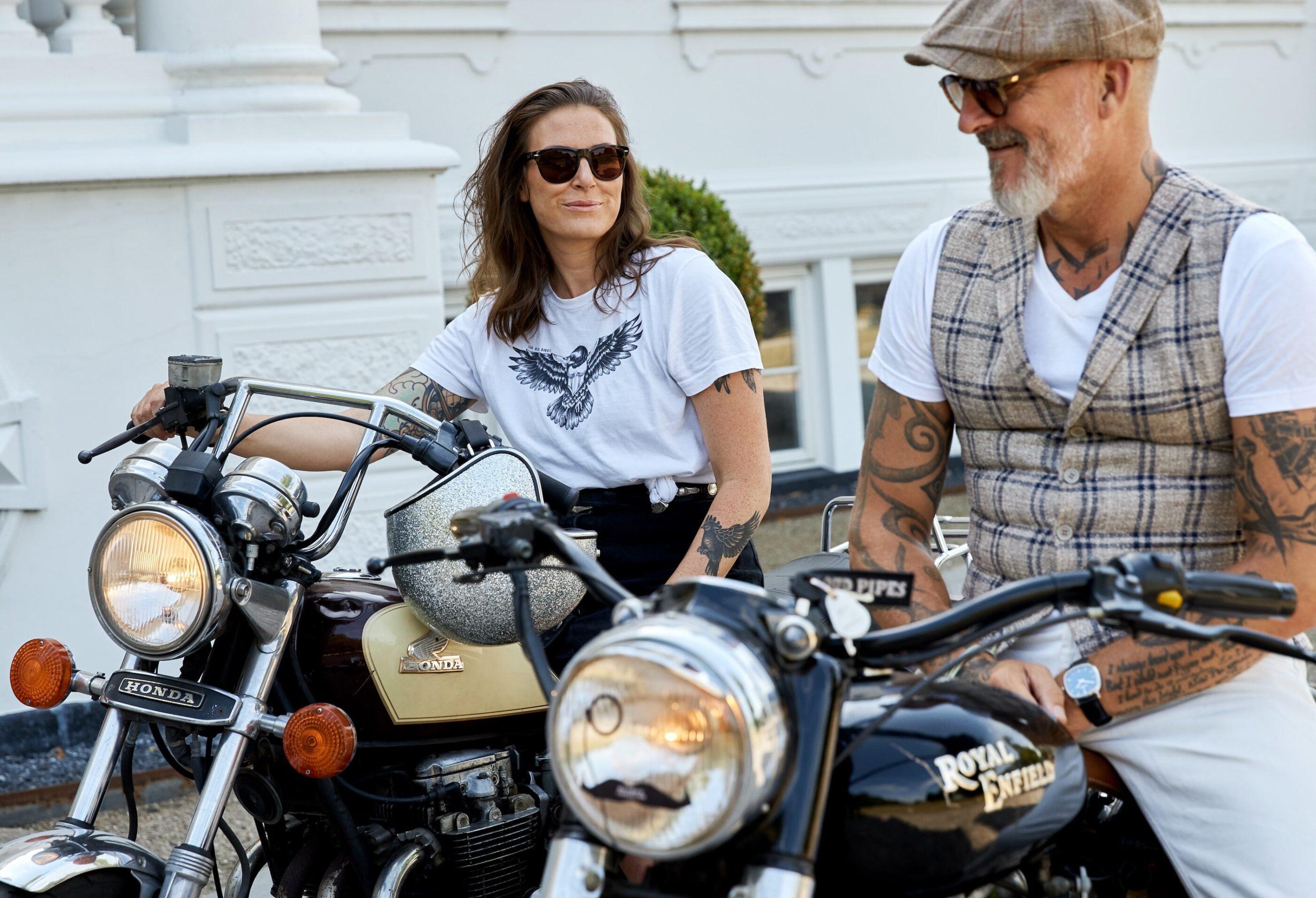 En mand og en kvinde med store tatoveringer sidder på motorcykler og smiler