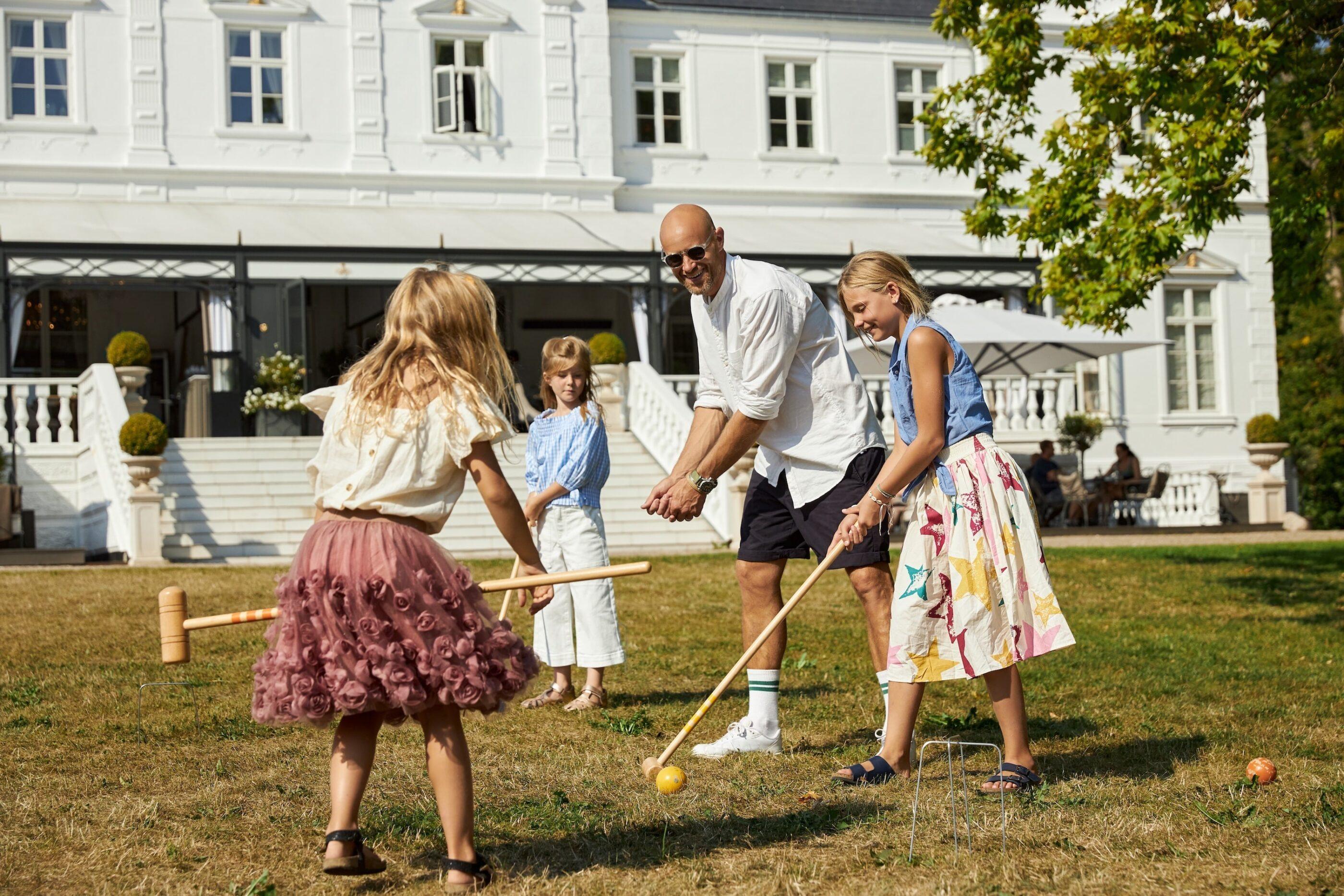 En voksen mand lærer 3 børn at spille kroket og simulerer med sine hænder hvordan man holder en kølle
