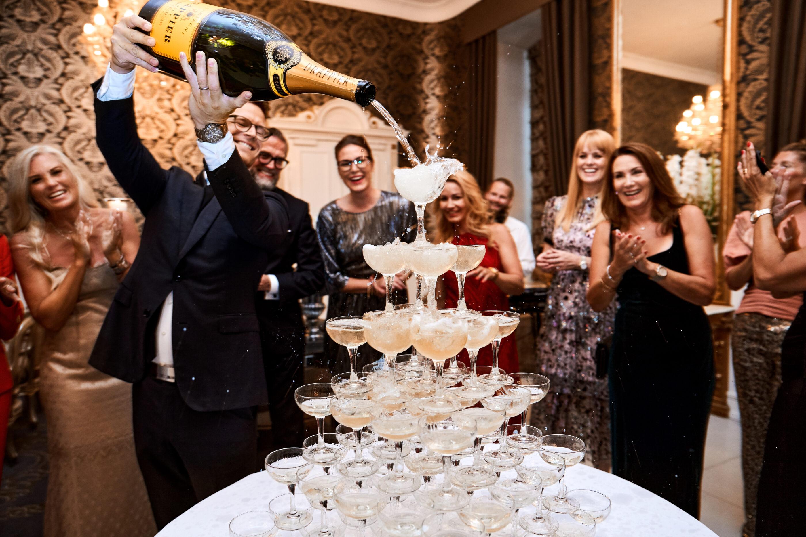 En mand hælder Champagne fra en kæmpe flaske udover et bjerg af champagne-glas som står oven på hinanden