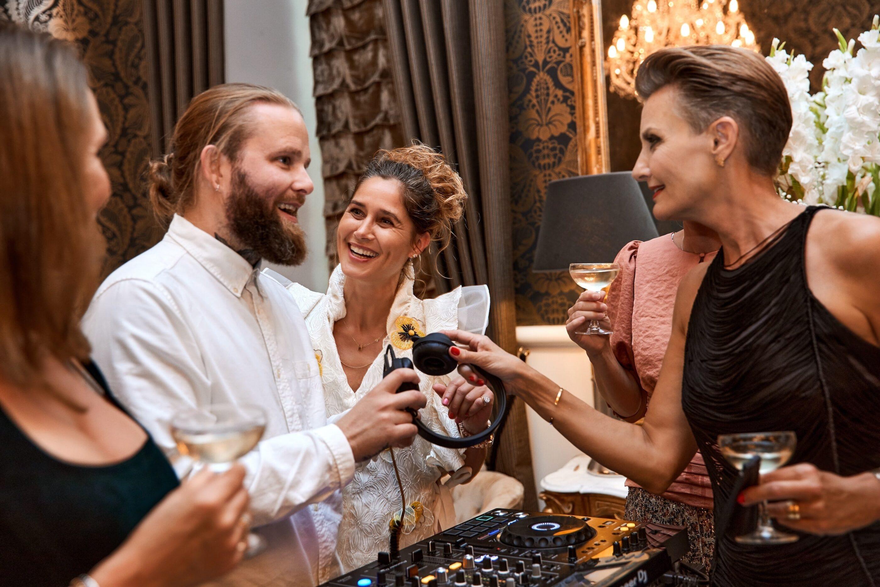 Under festen står 4 kvinder og snakker med DJ'en mens de har champagne glas i hænderne