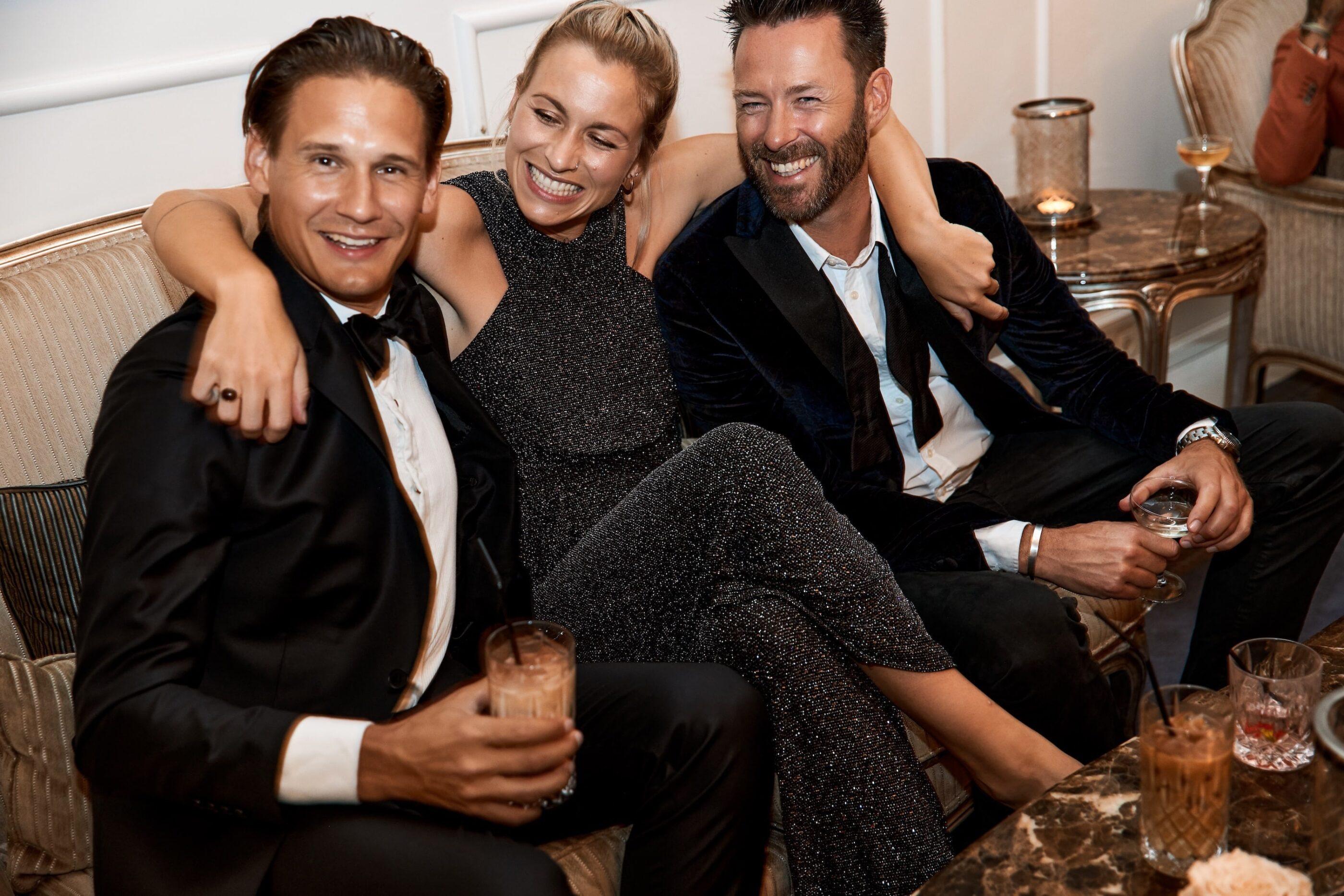 3 mennesker, en kvinde og to mænd, sidder på en sofa med drinks i hånden og hygger og smiler