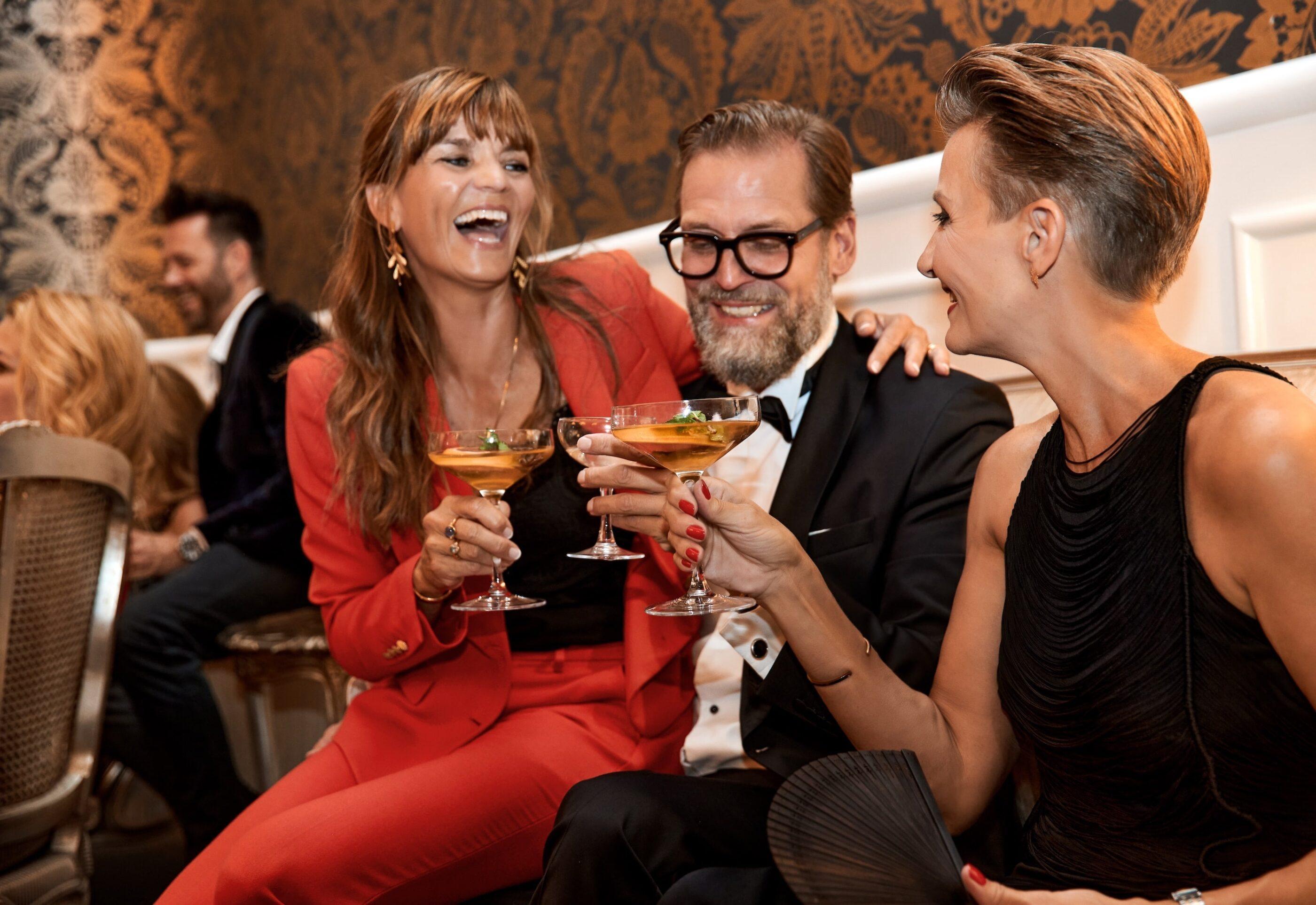En mand sidder med 2 kvinder og de skåler alle med deres drinks