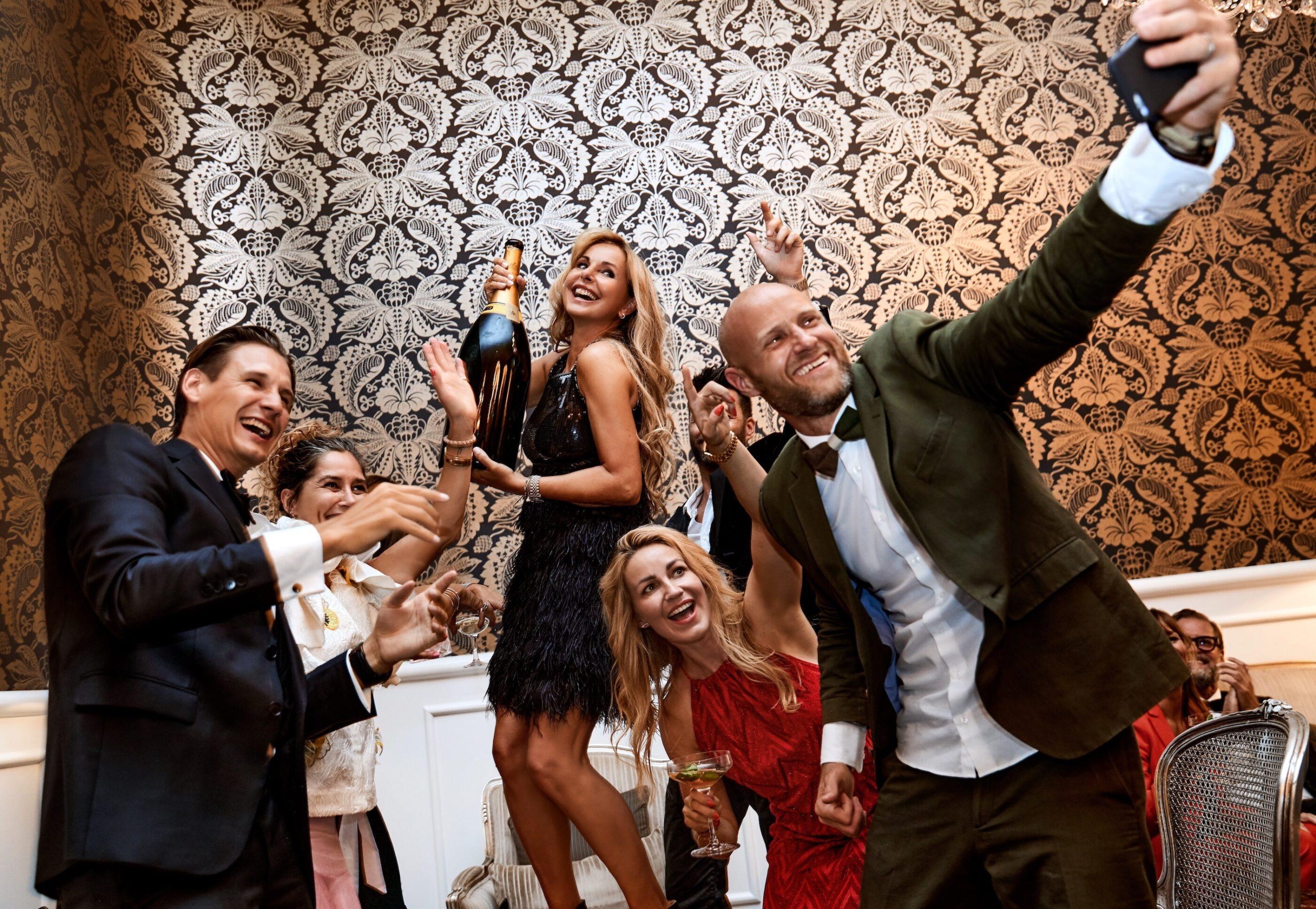En mand tager selfie med en gruppe af mennesker i balrummet mens de alle har det sjovt og en kvinde i midten holder en kæmpe champagne flaske
