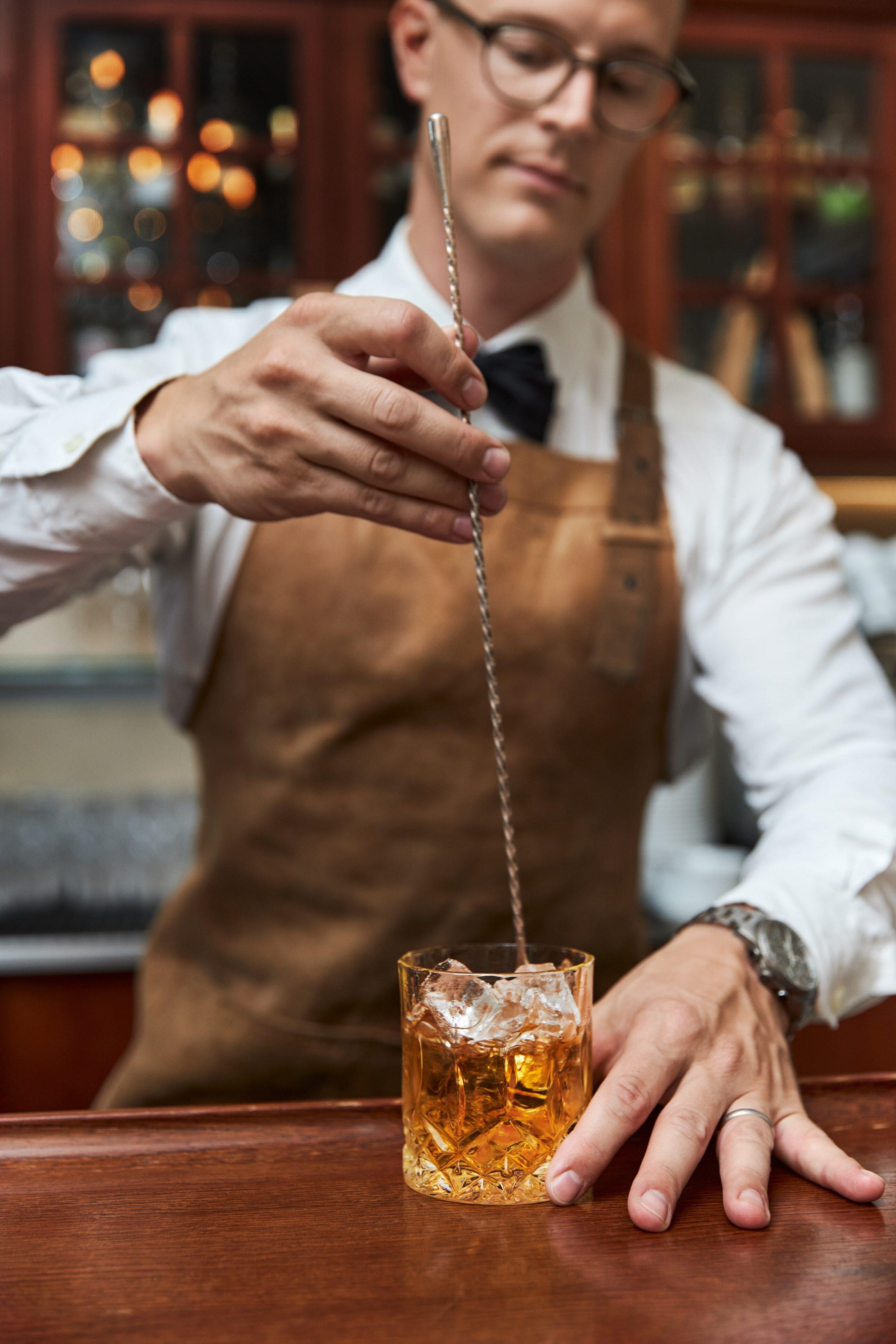 En bartender forbereder en drink med is ved desken