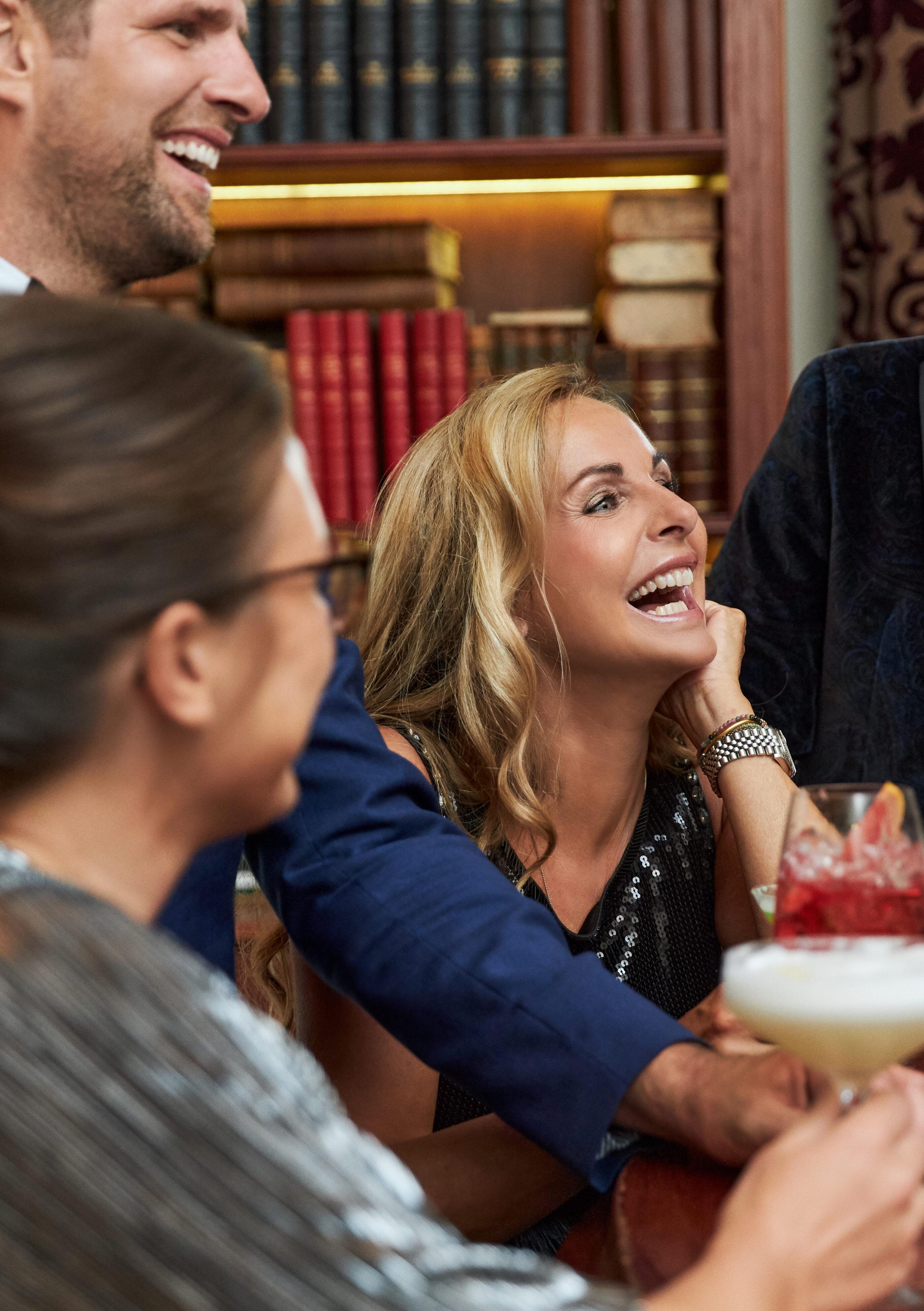 Nogle mænd og kvinder sidder ved baren med cocktail drinks og griner af noget sjovt