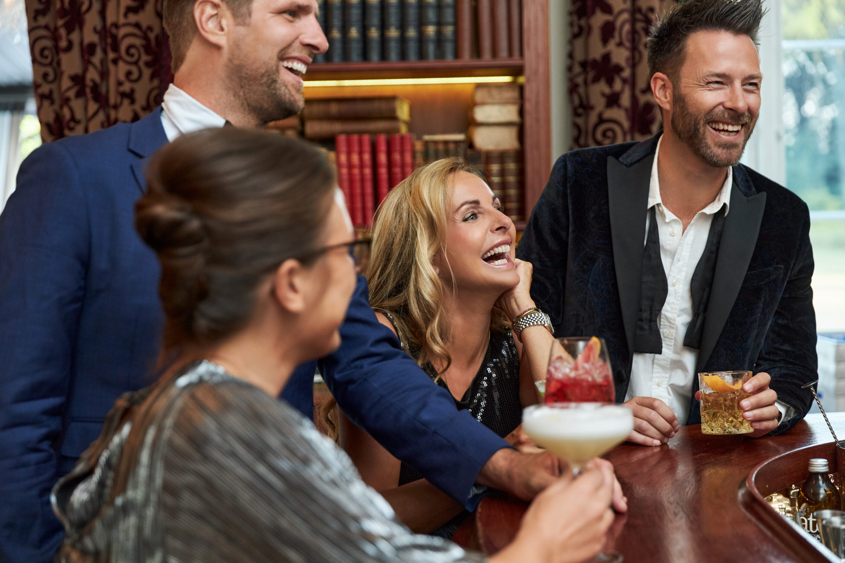 People laughing at the bar with drinks