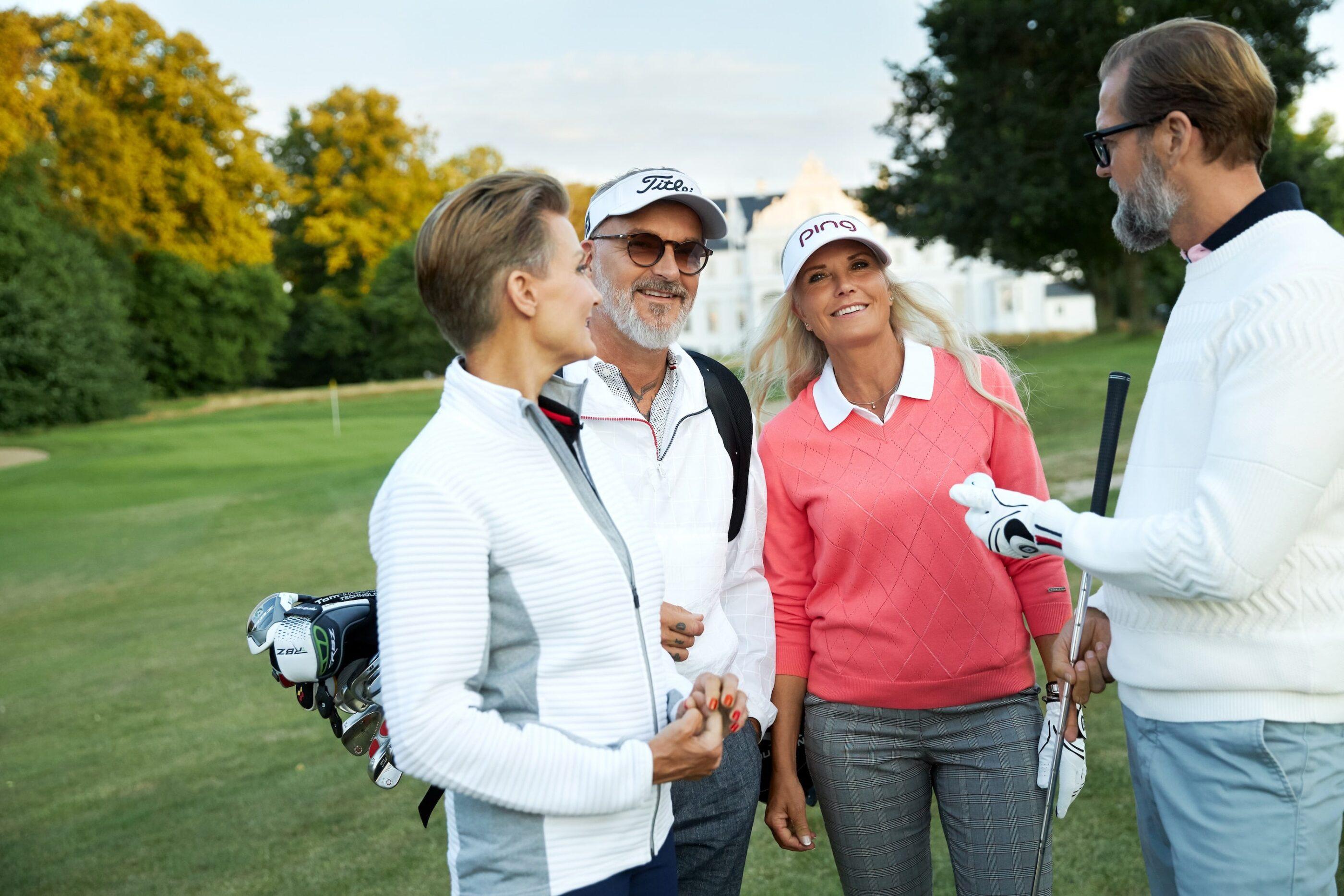 2 mænd og 2 kvinder iklædt golf tøj med golf udstyr inklusiv golfkøller står på en golfbane med hotellet i baggrunden og smiler
