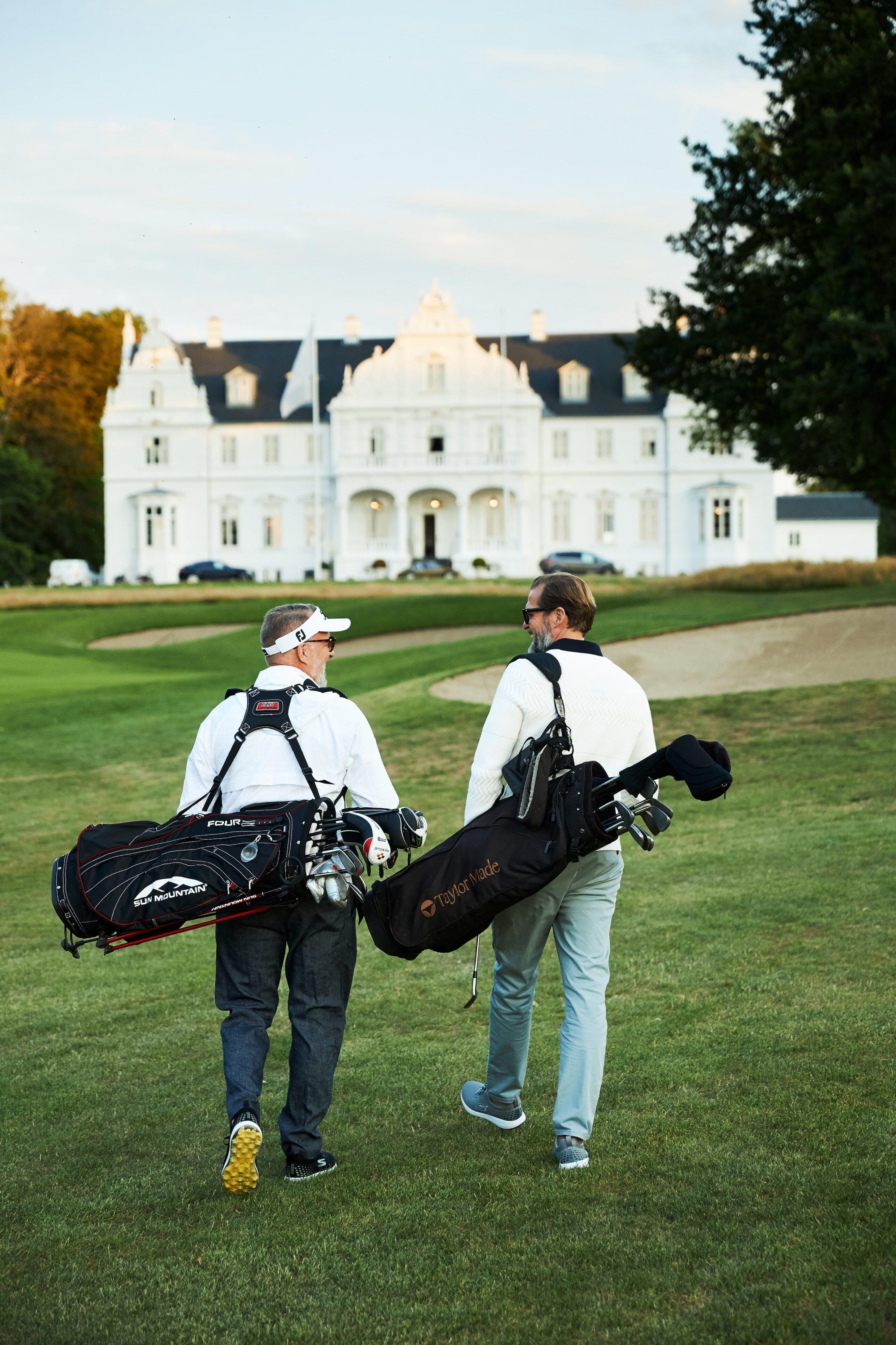 2 mænd går ned af golfbanen med golftasker i armen med udsigt til hotellet i foregrunden