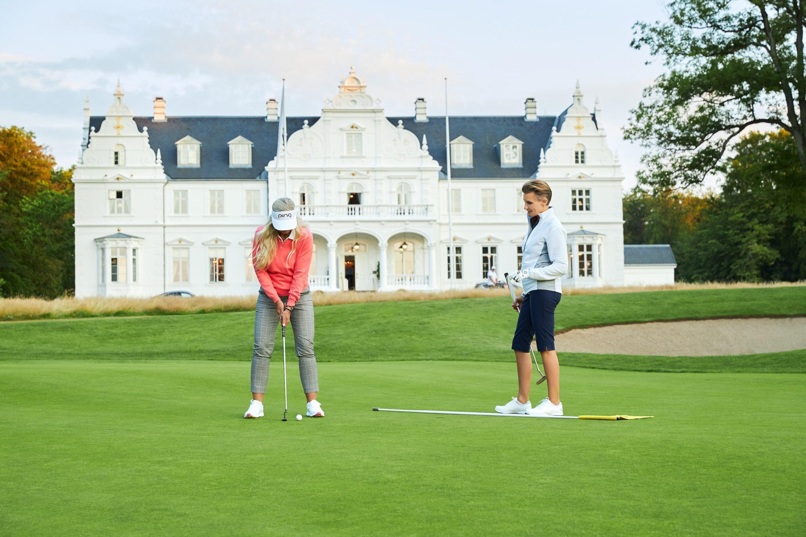 En mand og en kvinde iført golf tøj står på golfbanen med hotellet i baggrunden og kvinden skal til at slå til en golfboldt med sin kølle