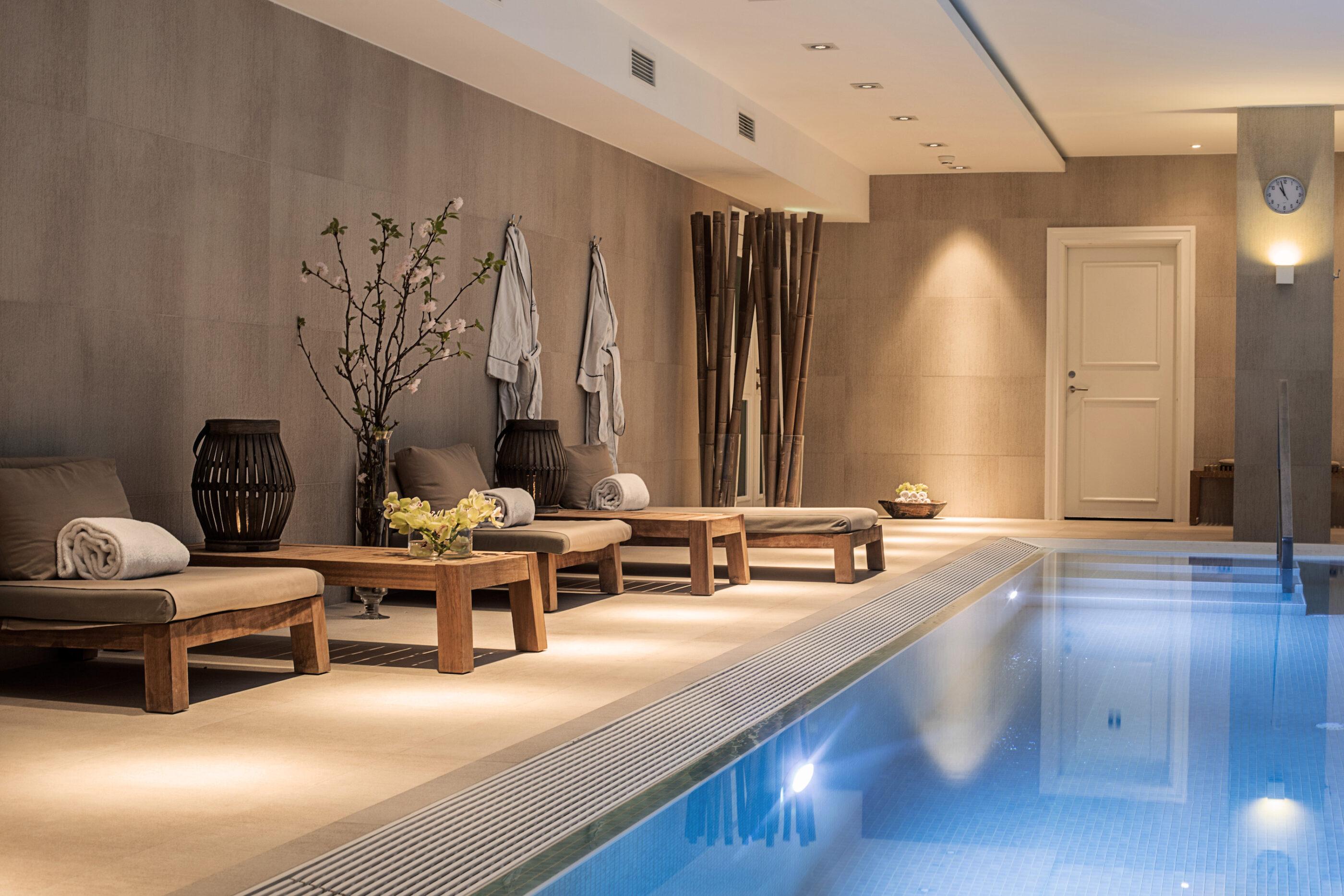 3 liggestole med håndklæder og kåber der hænger på væggen, samt belyst Infinity pool