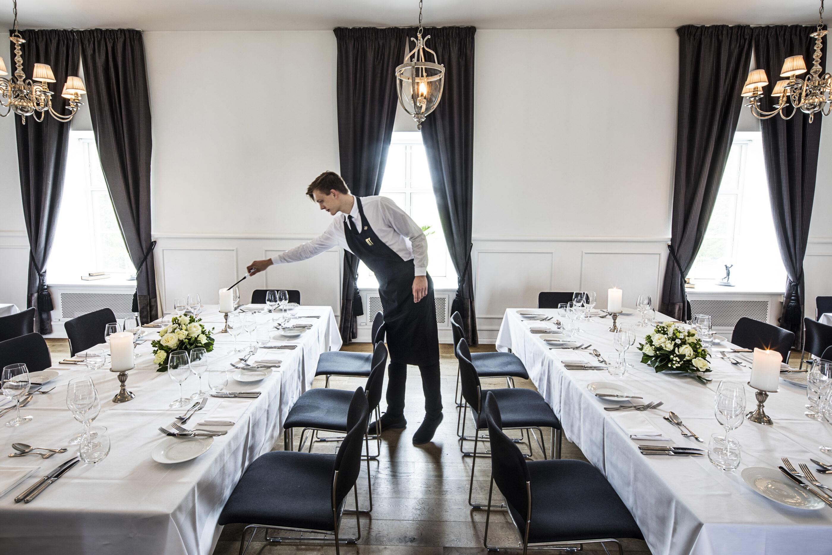 Kokkedal Slot medarbejder tænder for stearinlys ved flere middagsborde som ligger parallelt over for hinanden
