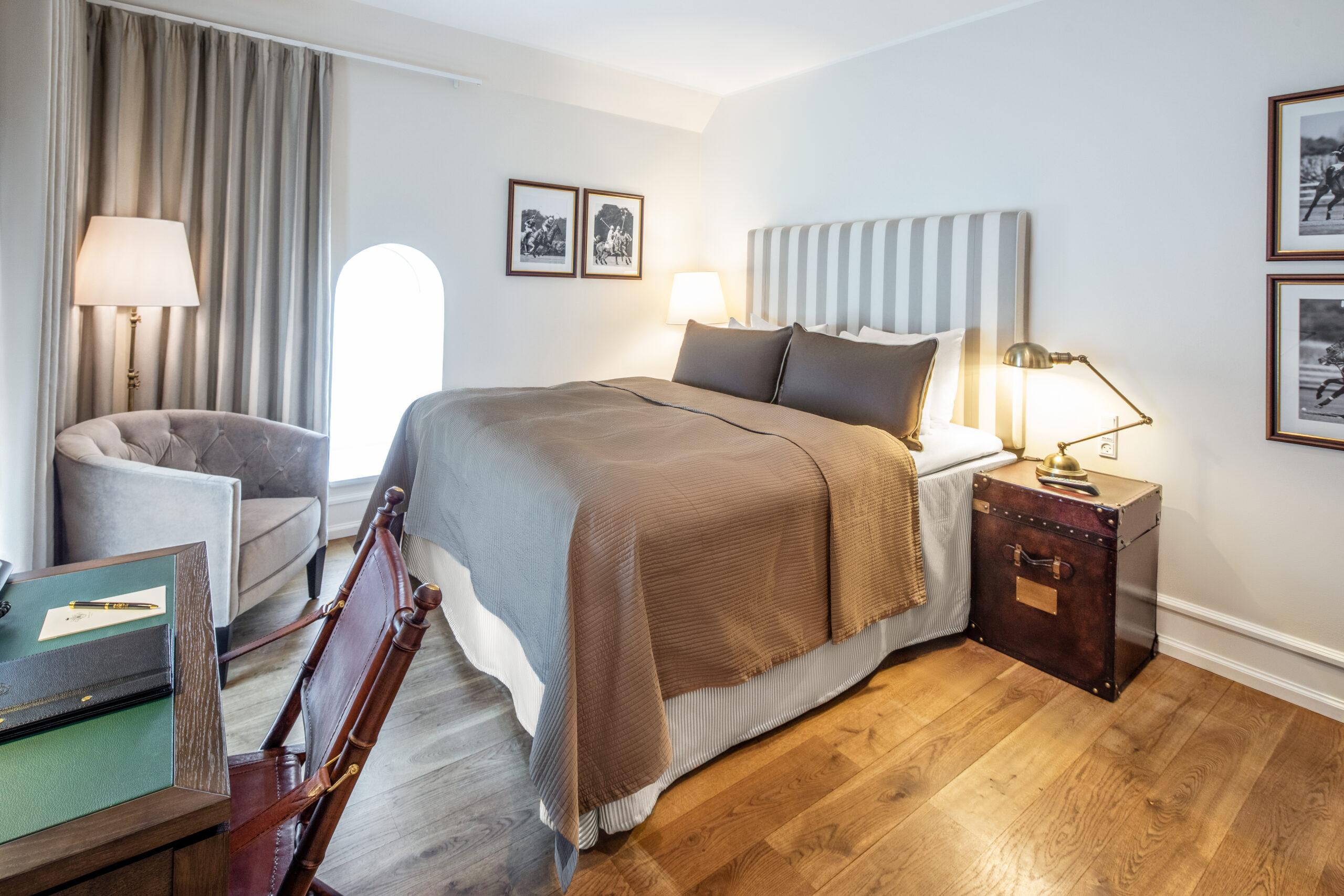 Standard dobbeltværelse med gammeldags sengebord og lampe, samt klassisk designet skrivebord og stol med fin pen og notesblok samt lædermappe på bordet