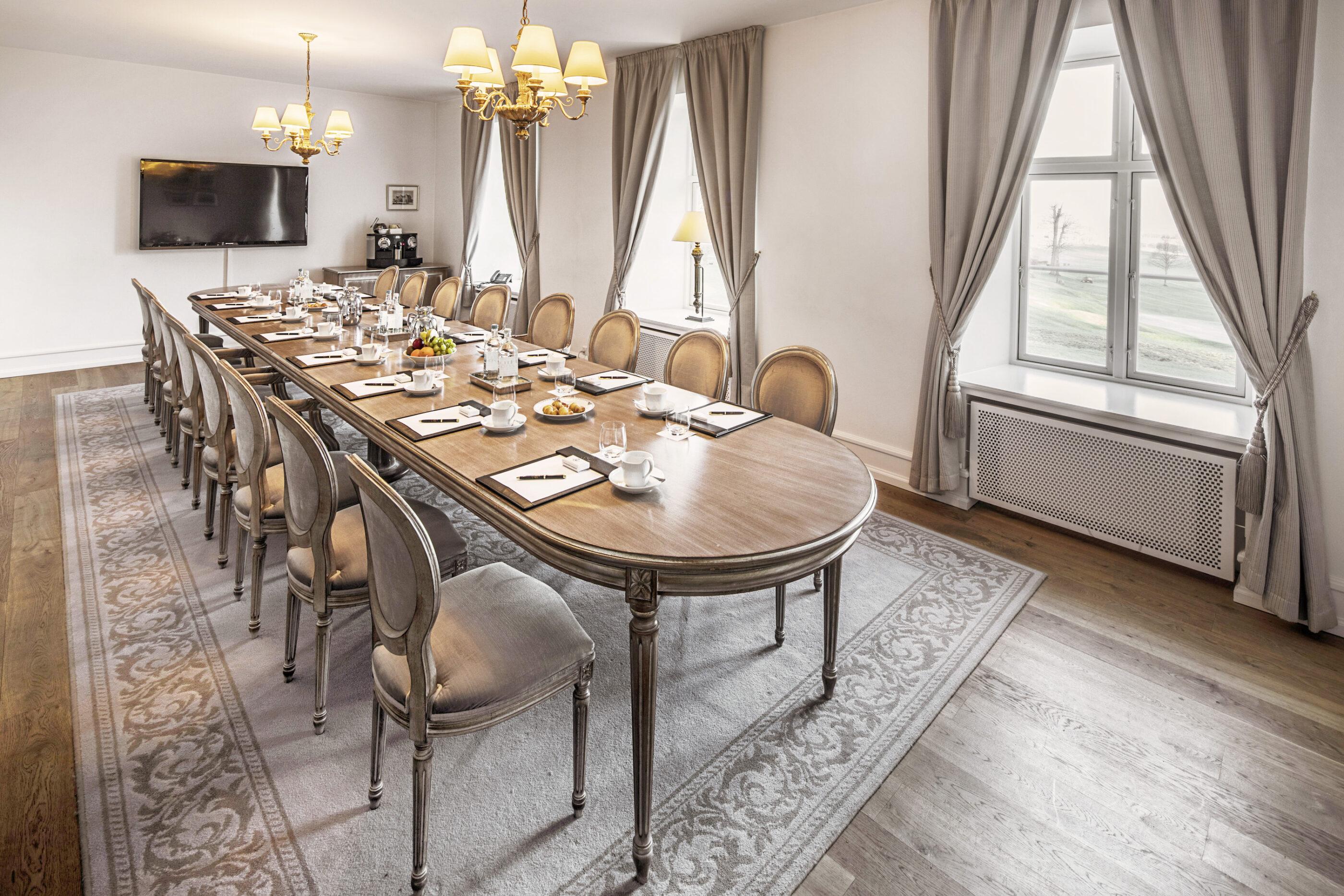 Mødelokale med et langt bord som har runde kanter og på bordet ligger pen og papir klar, med kaffe kopper ved hver stol