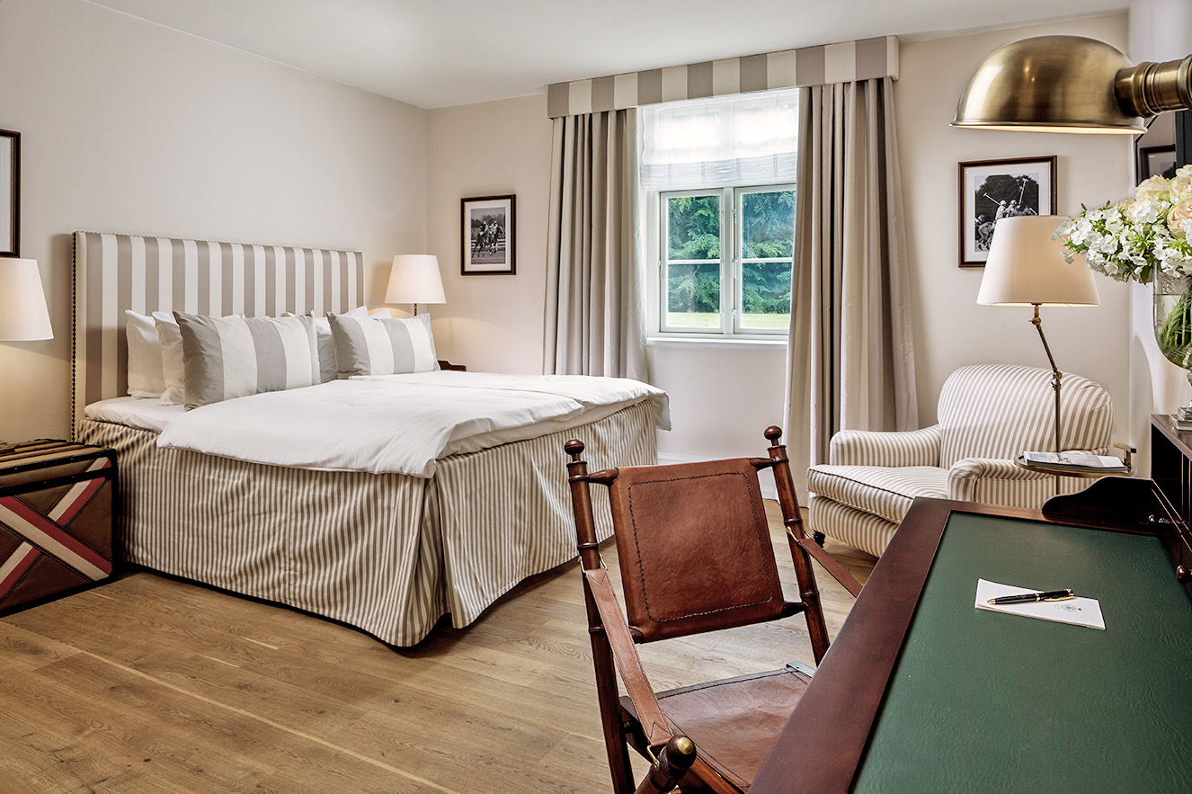 Et soveværelse med udsigt til haven og skoven, og et træbord med grøn overflade samt træstol og pen og notepapir på bordet.