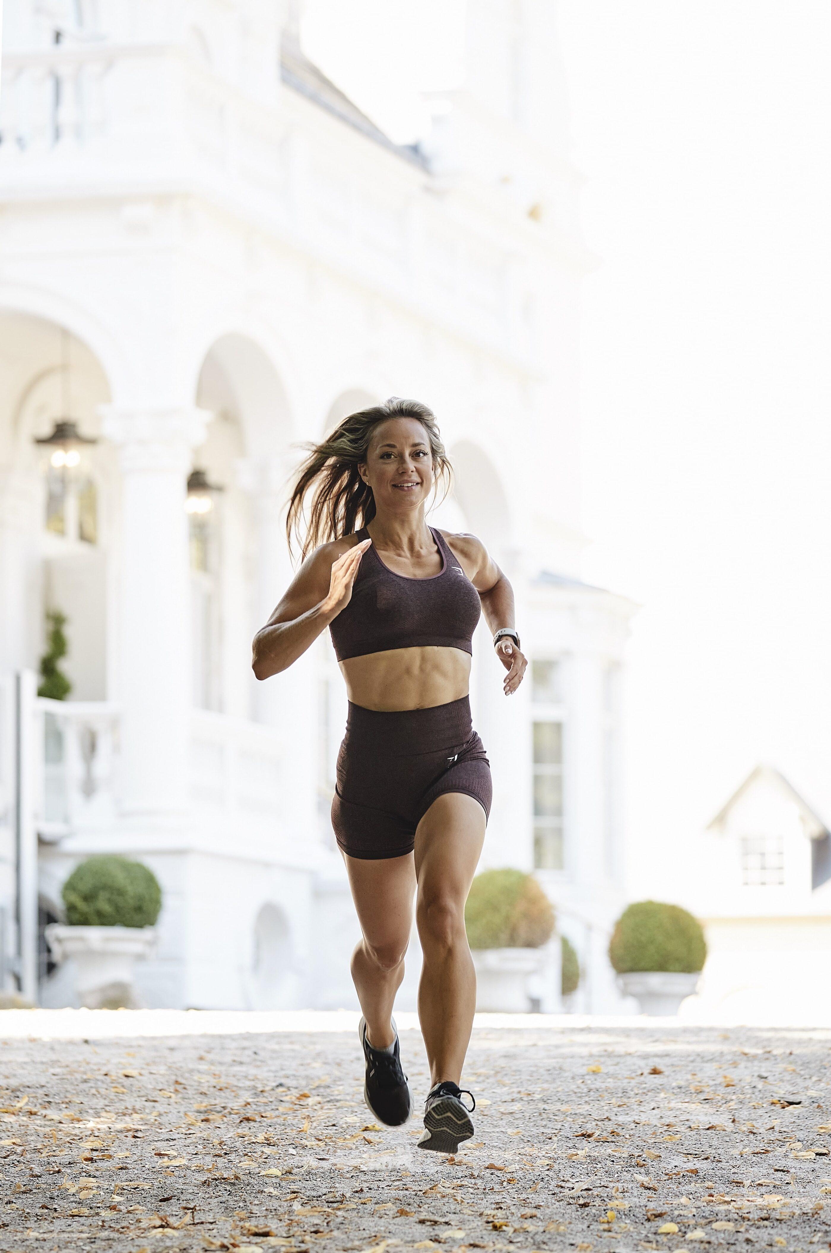 En kvinde iført træningstøj løber i hotellets går